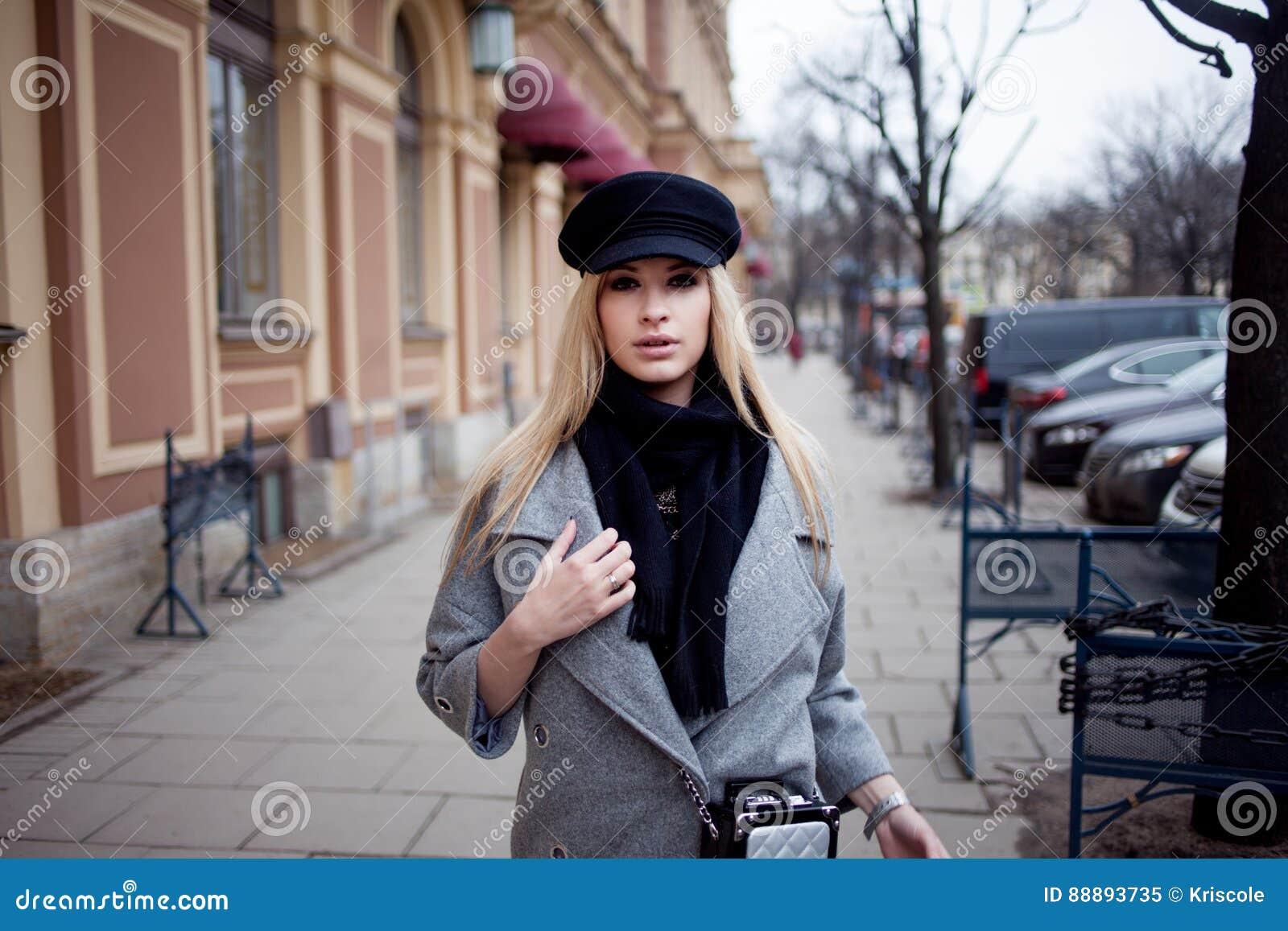 年轻人,熟悉内情和有吸引力白肤金发一个时髦的帽子的走在城市附近,女孩和一件灰色外套