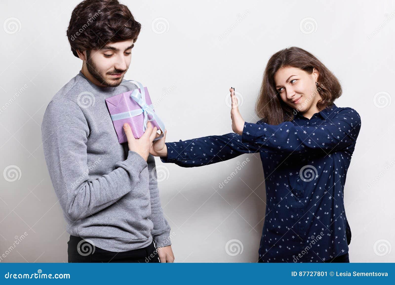 人们和关系 给被触犯的妇女礼物盒,女孩的年轻人拒绝接受礼物 有的夫妇有些问题我