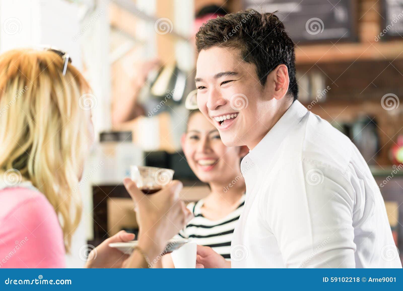 人们获得咖啡和乐趣在亚洲咖啡馆