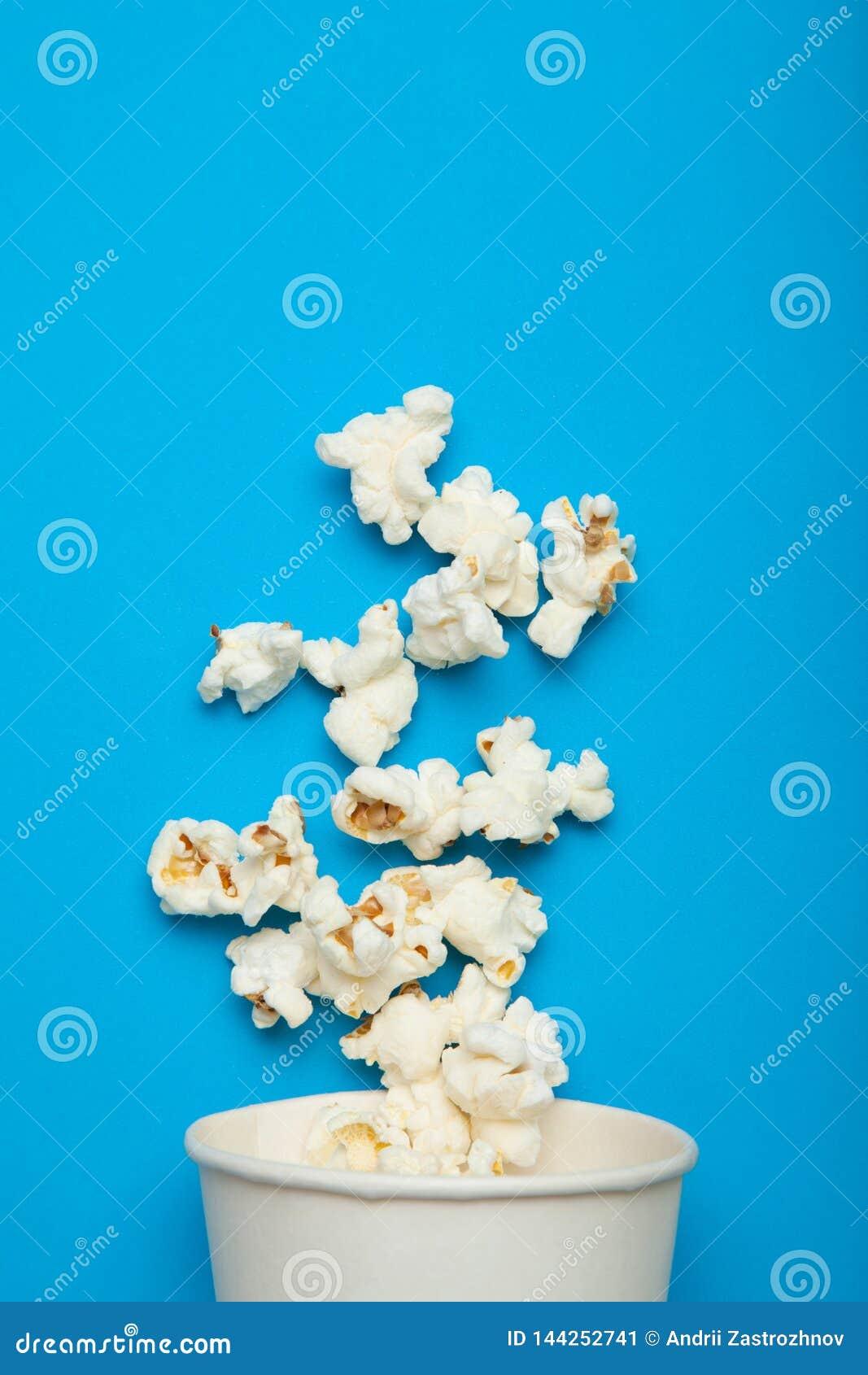 从一个白皮书杯子的浮动玉米花在蓝色背景