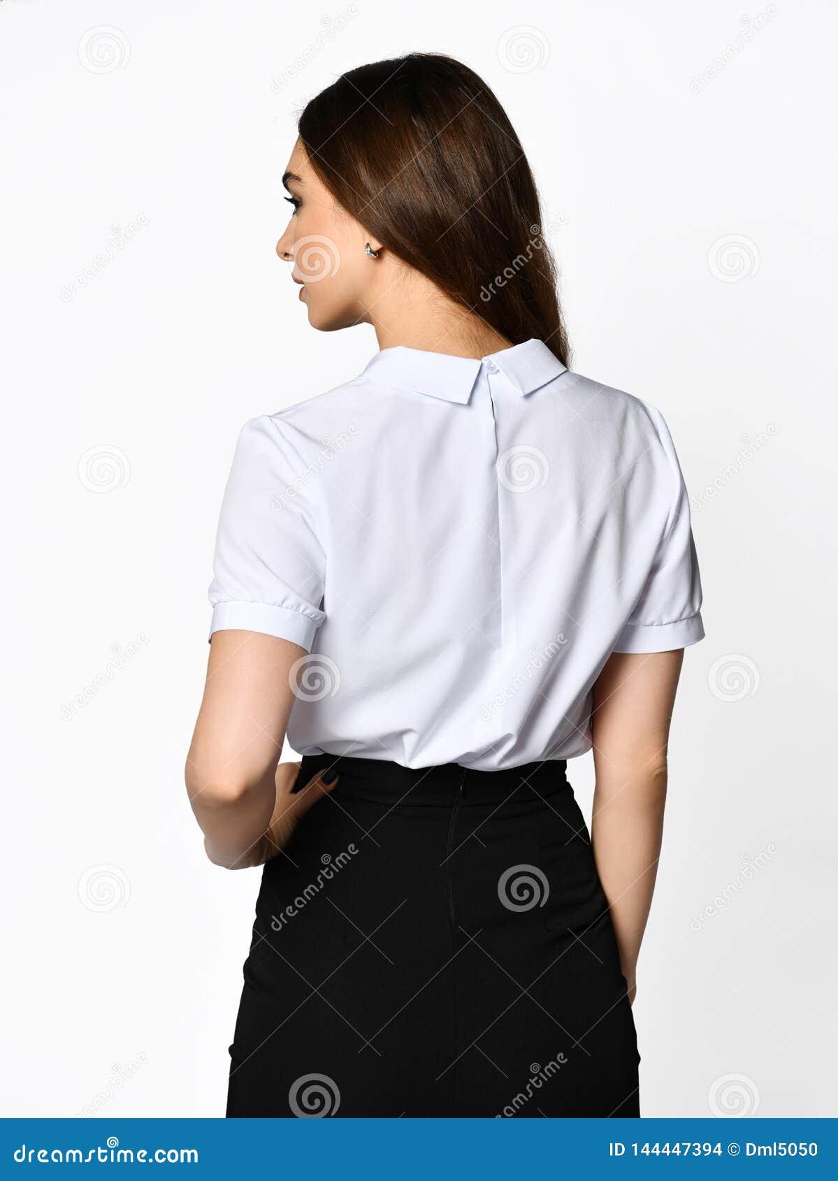 从后面 摆在轻黑暗的办公室衣服的年轻美女 轻的女衬衫和黑暗的铅笔裙子