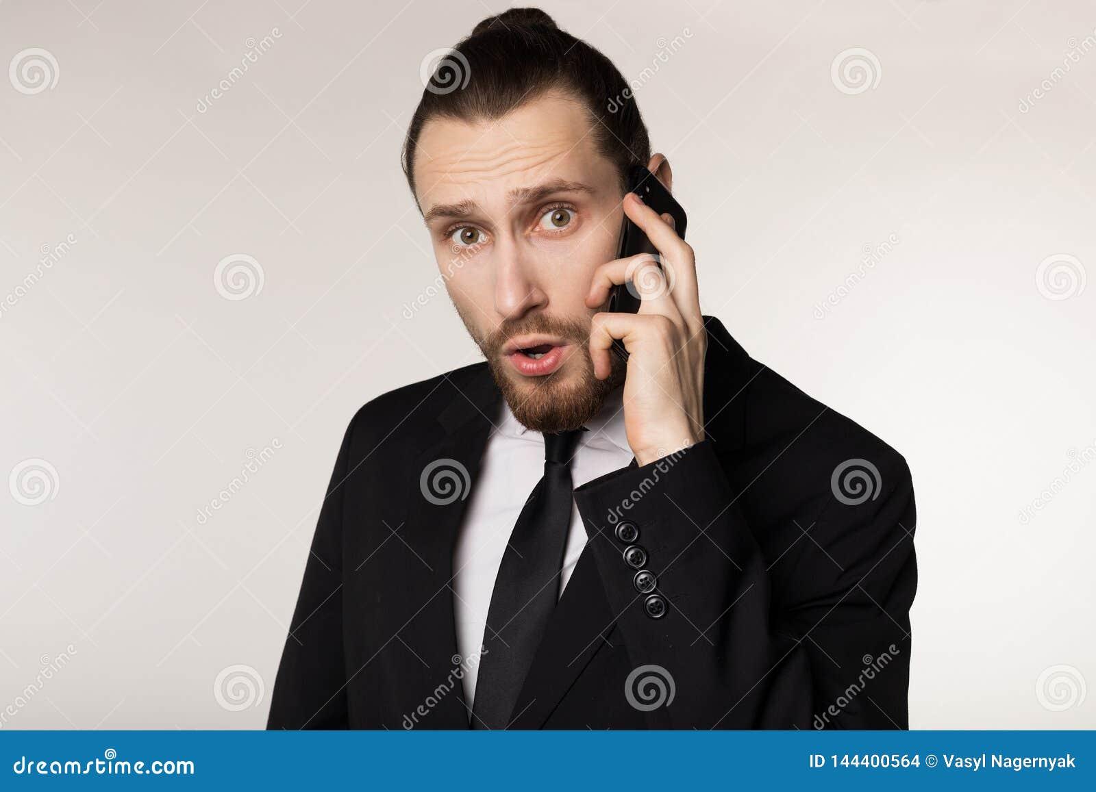 从商务伙伴的听见的新闻在黑衣服的惊奇的有胡子的年轻商人画象的腰部
