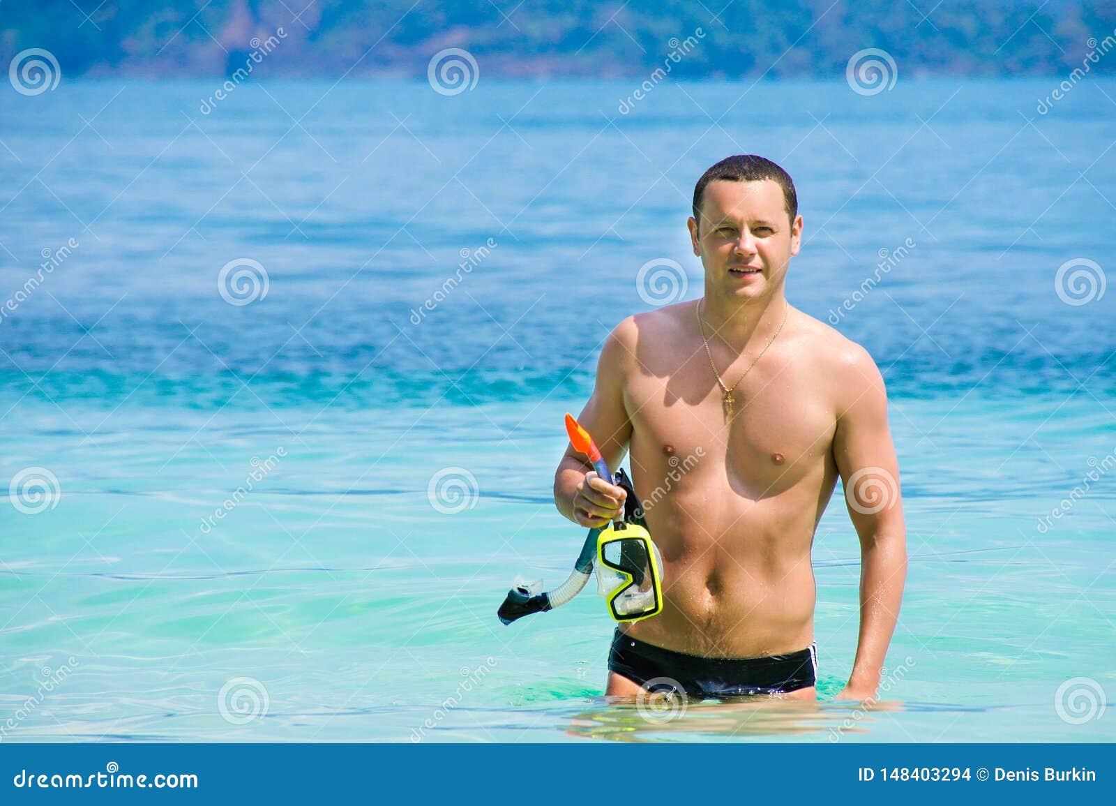 从海出来的年轻人在游泳以后 愉快的人在度假 一个人走海滨