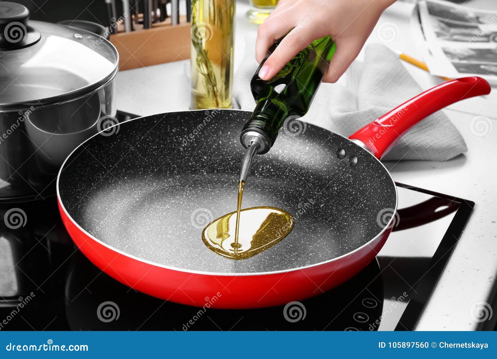 从瓶的妇女倾吐的油到煎锅里