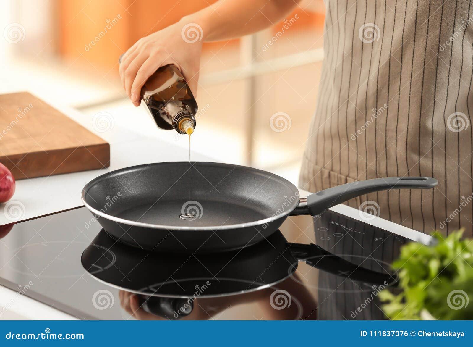 从瓶的妇女倾吐的烹调用油到煎锅里