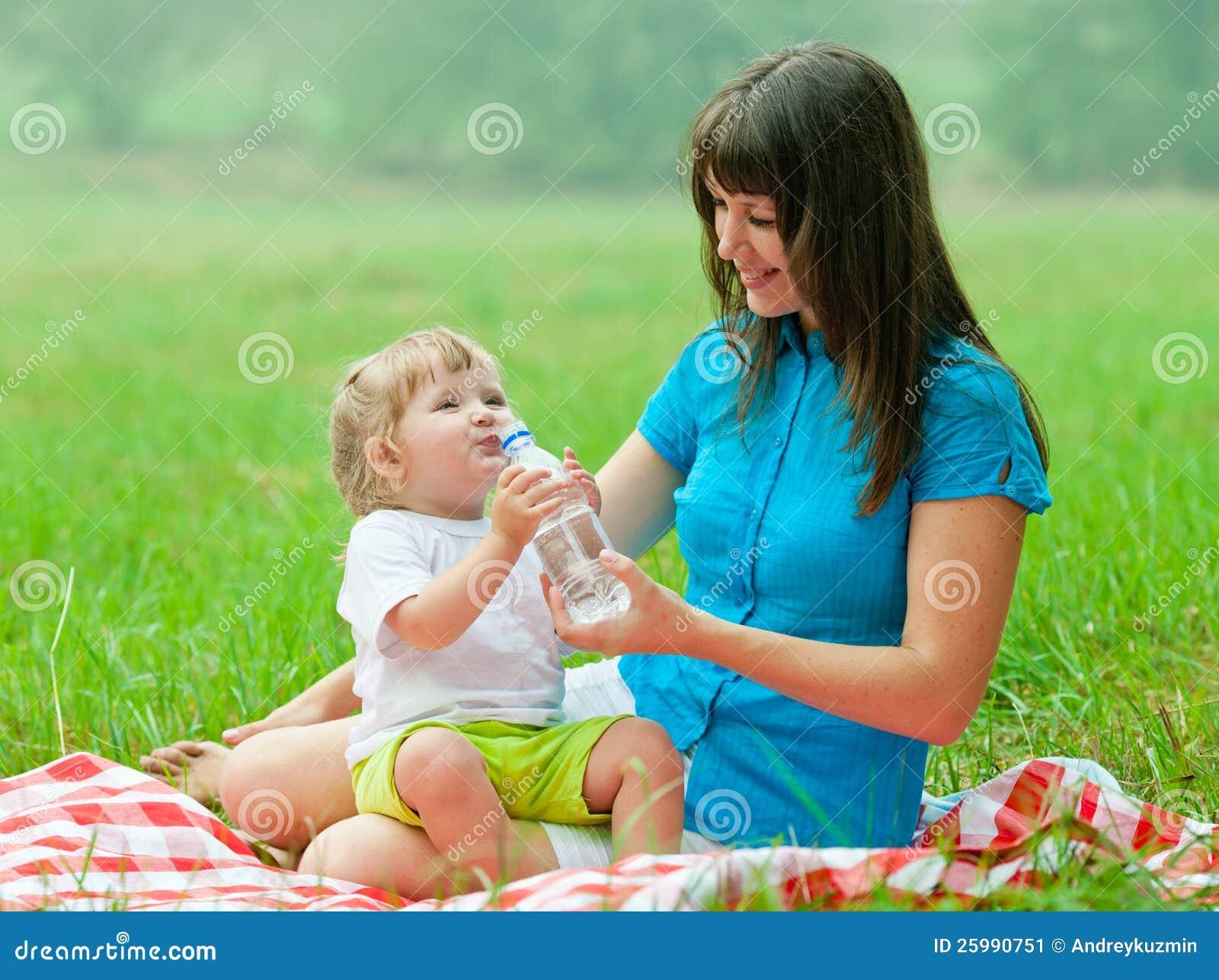 从瓶的愉快的母亲和孩子饮用水