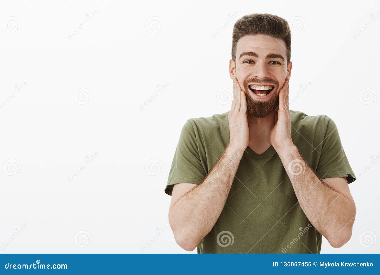 从笑和微笑受伤的面颊 发笑愉快的弱拍可爱的有胡子的成年男性画象在橄榄色的T恤杉的