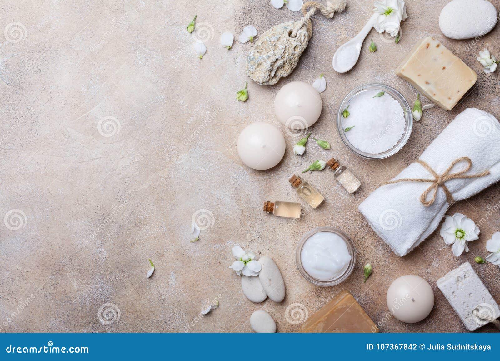 从身体关心和秀丽threatment产品的温泉设置与在石背景顶视图的花 健康和健康概念