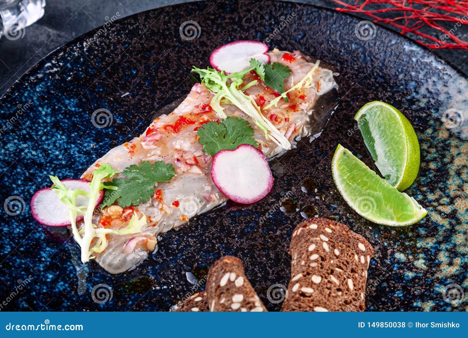 从雪鱼的新和鲜美cebiche 从生鱼片的海鲜盘 与石灰的Ceviche和在黑暗的板材microgreen服务 ??