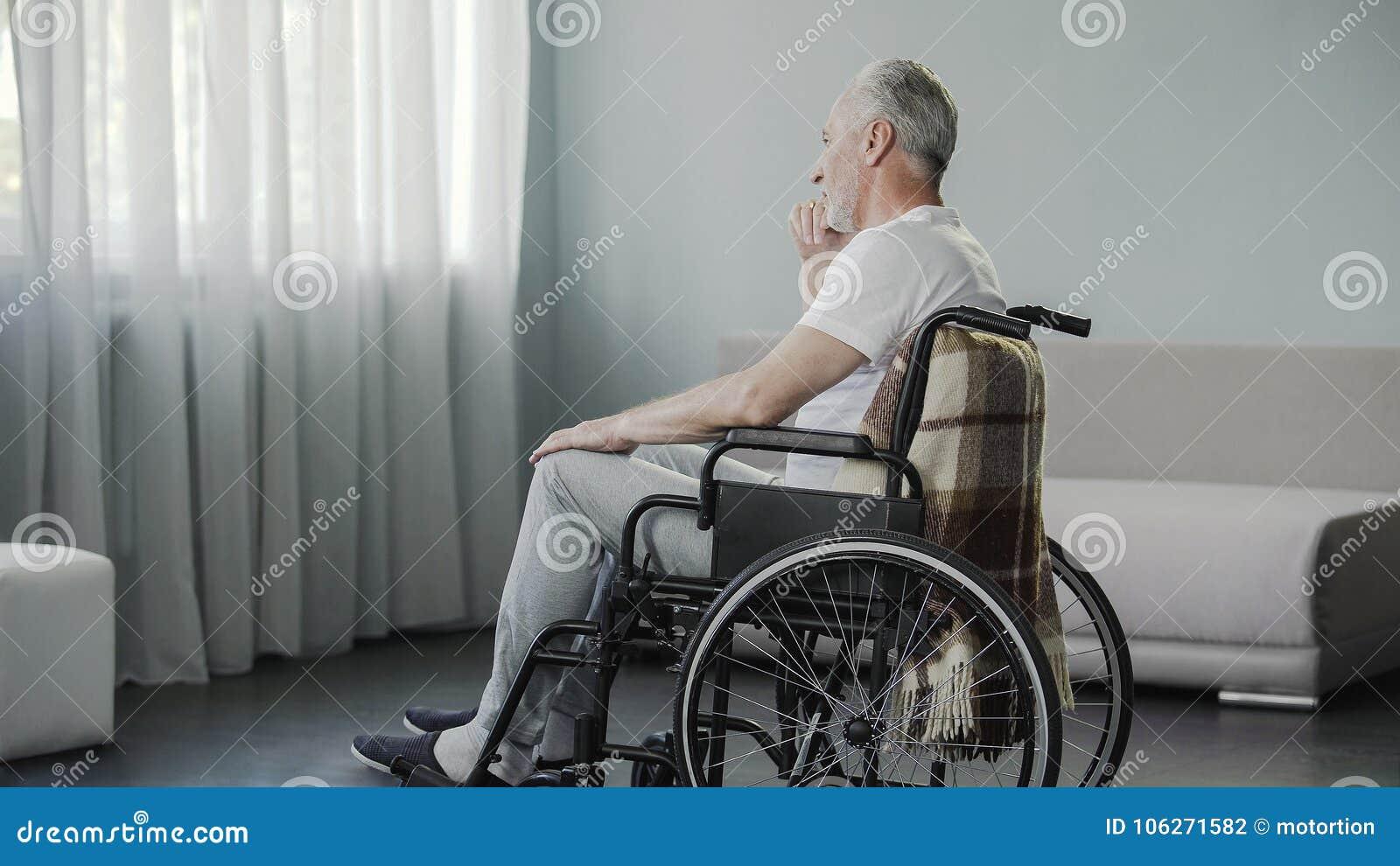 他的坐在轮椅的60s的孤独的人在健康康复中心