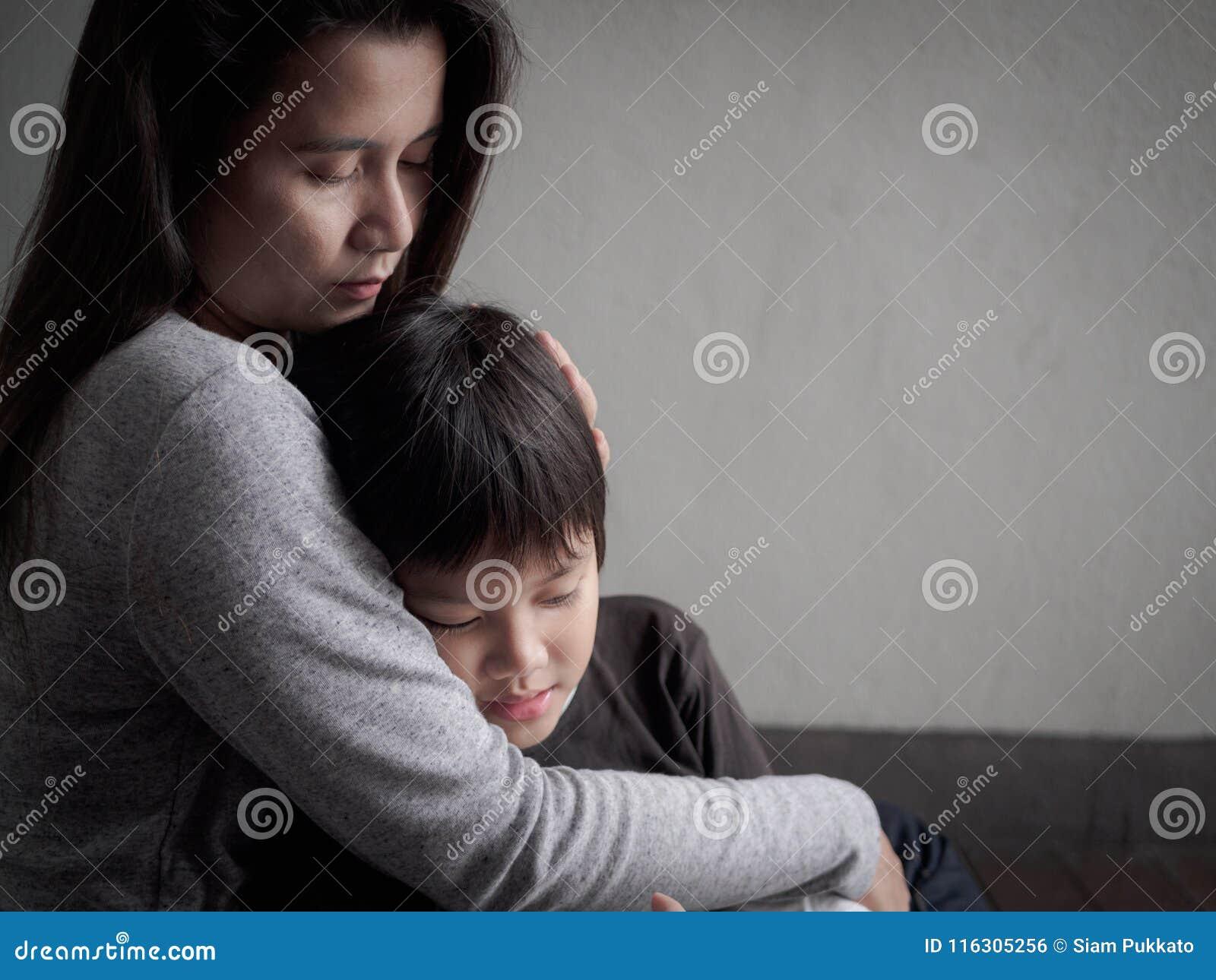 他的母亲在家拥抱的哀伤的小男孩