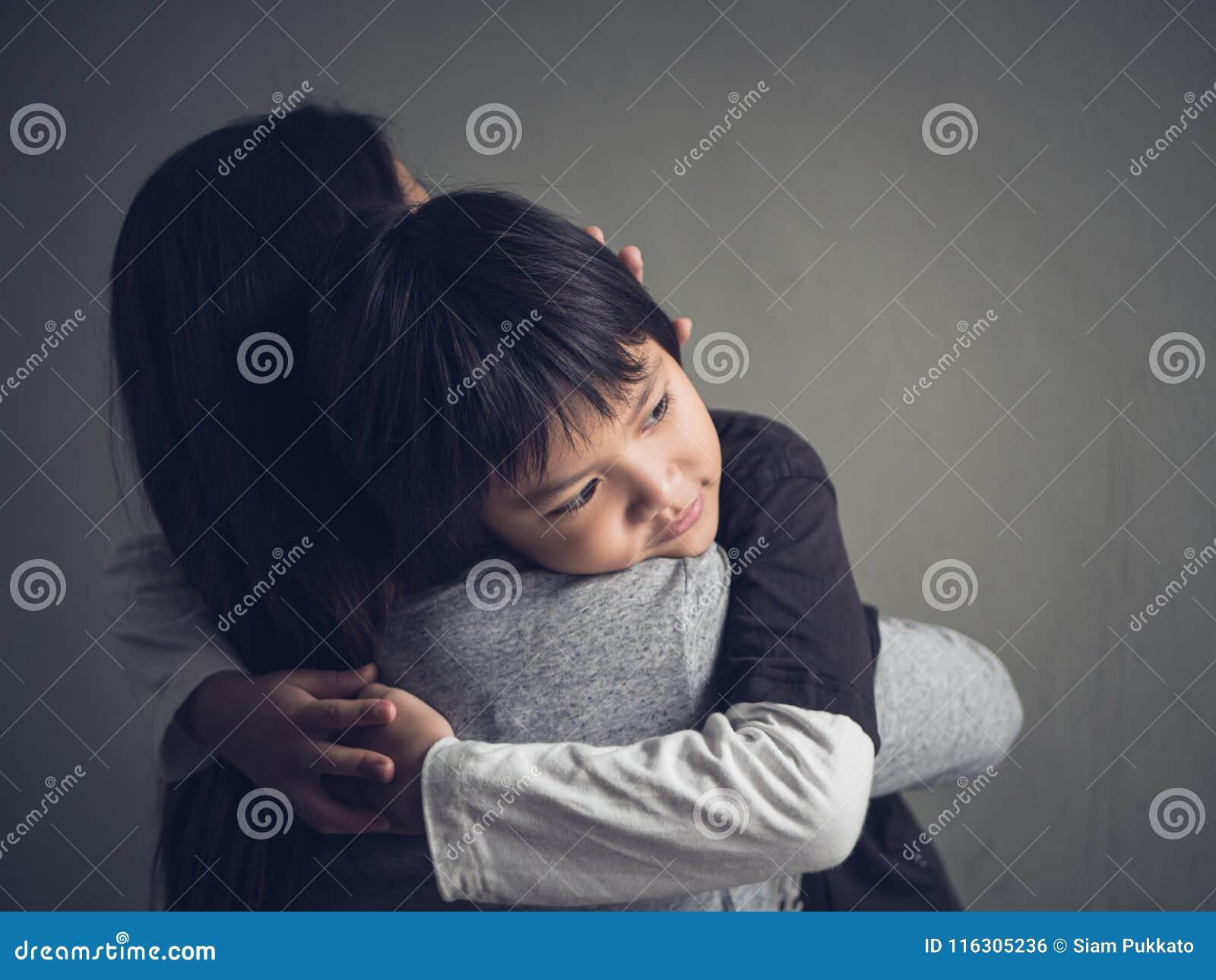 他的母亲在家拥抱的特写镜头哀伤的小男孩