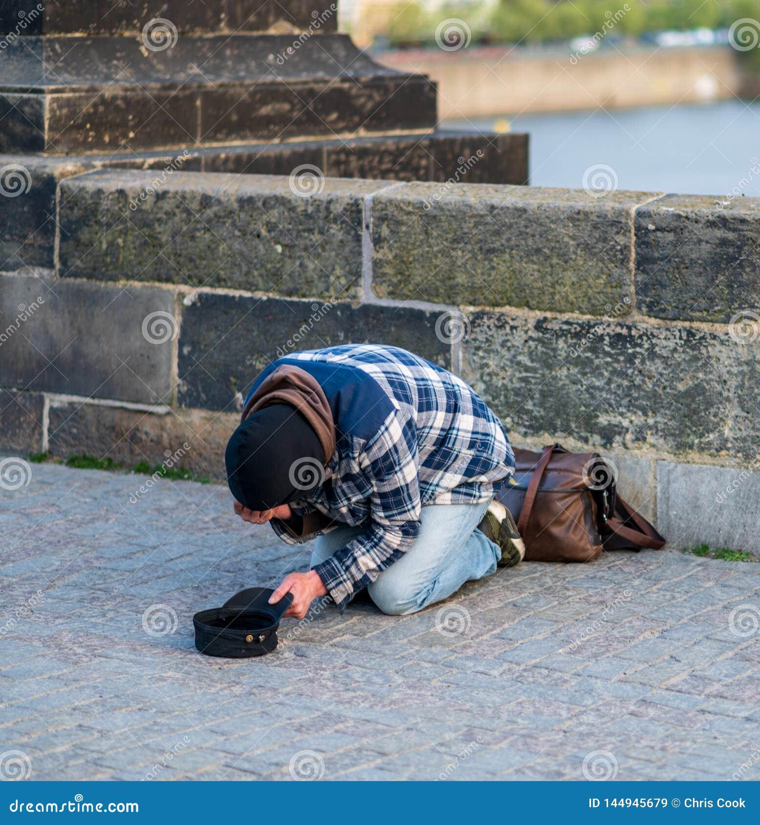 他的膝盖的冷的无家可归的人乞求为从游人的金钱查理大桥的在布拉格-春天2019年
