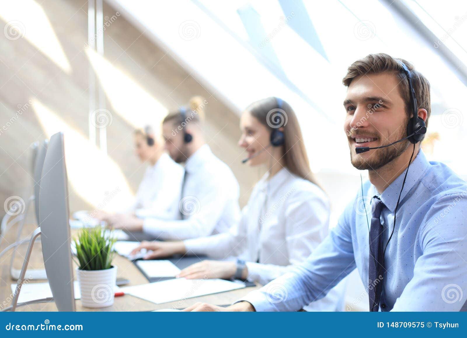 他的队陪同的电话中心工作者画象  微笑的用户支持操作员在工作