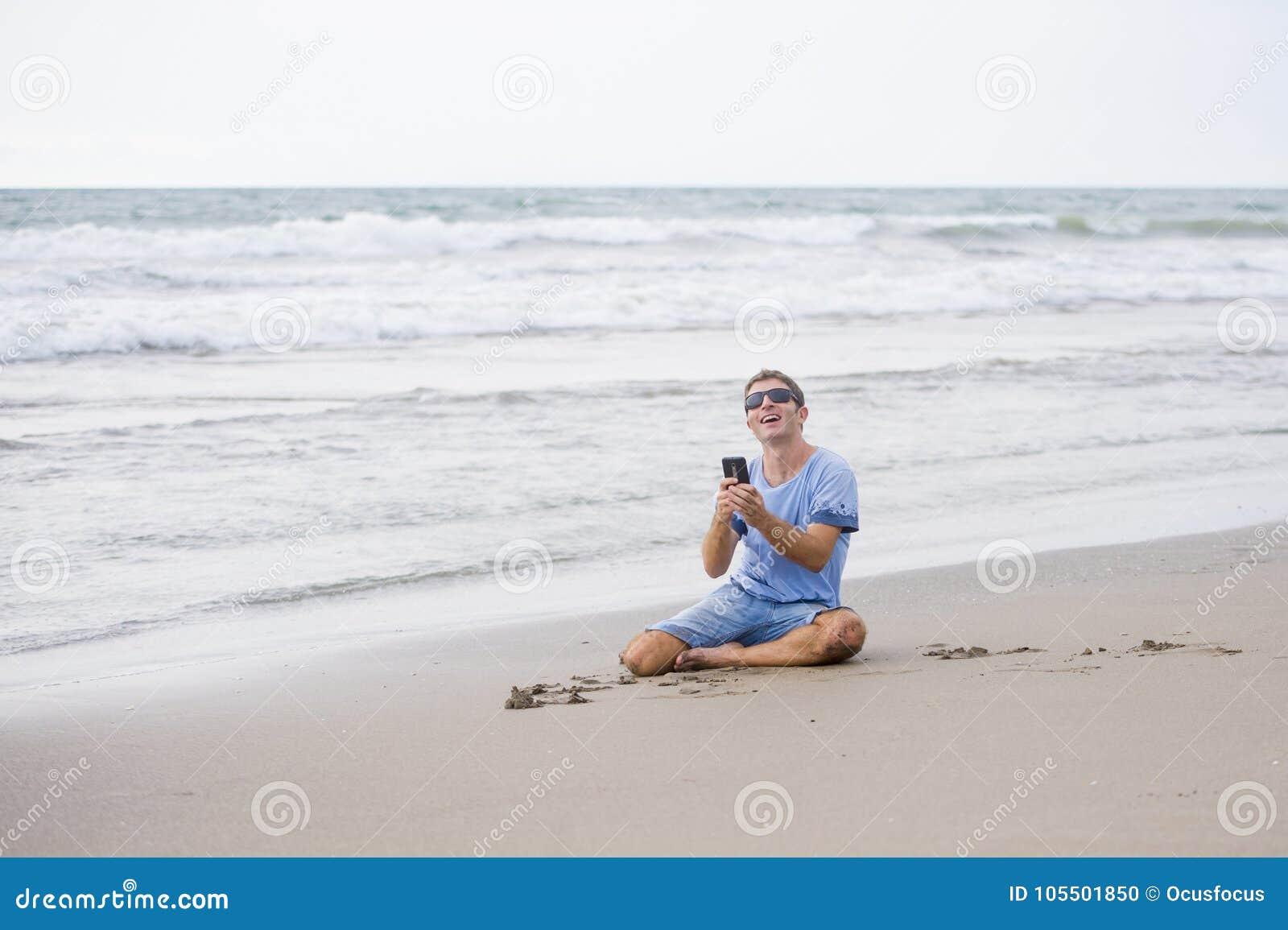 他的30s的可爱和英俊的人坐沙子在海滩放松了笑在海前面的发短信在流动pho