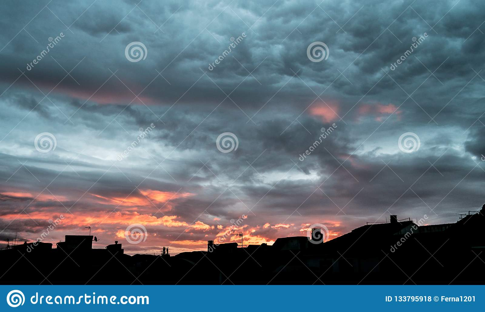令人惊讶的多云天空日出 深黄在美好的日出的风暴可怕剧烈的云彩与在风暴的移动的云彩