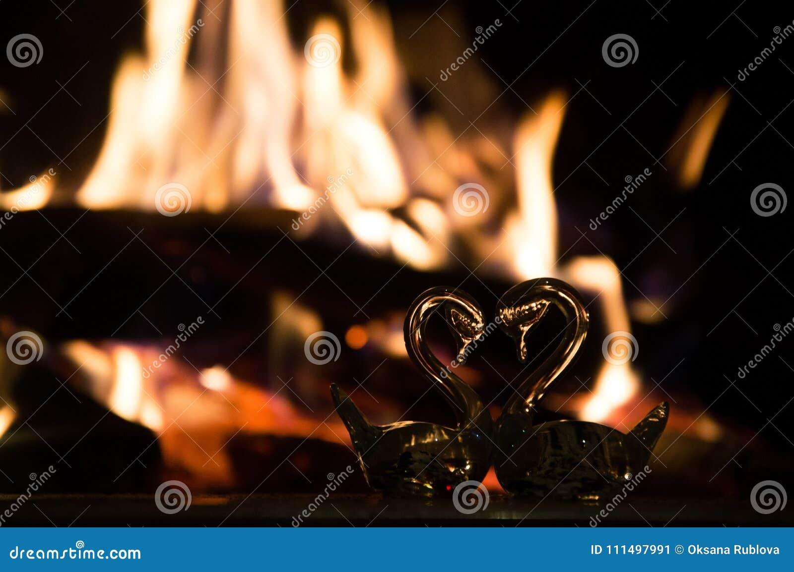 以心脏的形式两只玻璃天鹅在壁炉附近