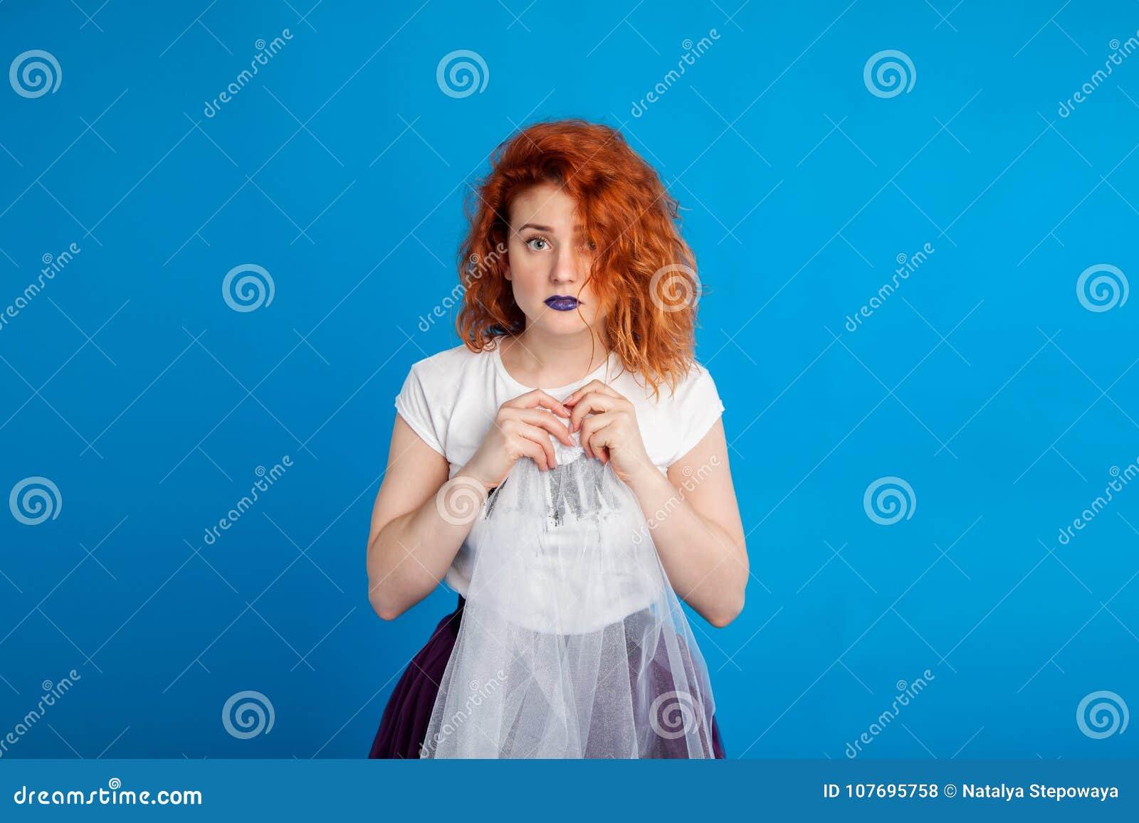 仿照废物样式的迷茫的红发女孩 情感概念 在明亮地蓝色m背景 安置文本