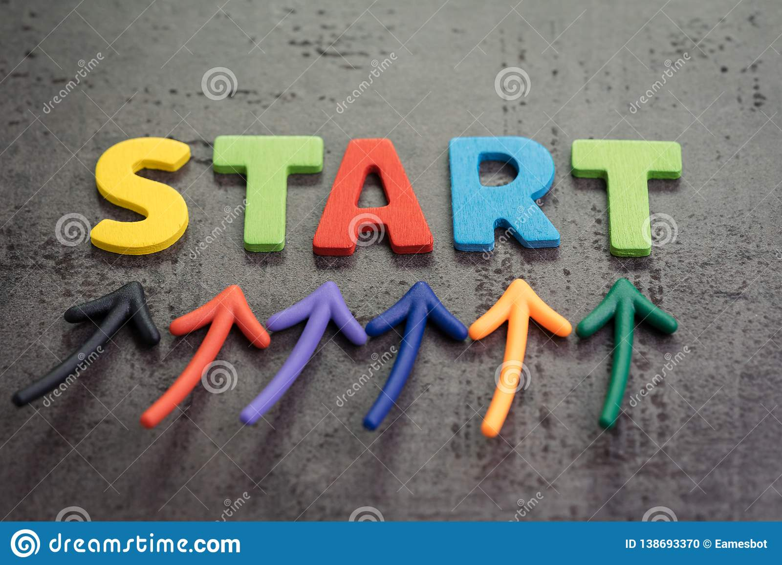企业开始或开始新的生活旅途概念,五颜六色的箭头指向由在黑板水泥墙壁上的词开始决定