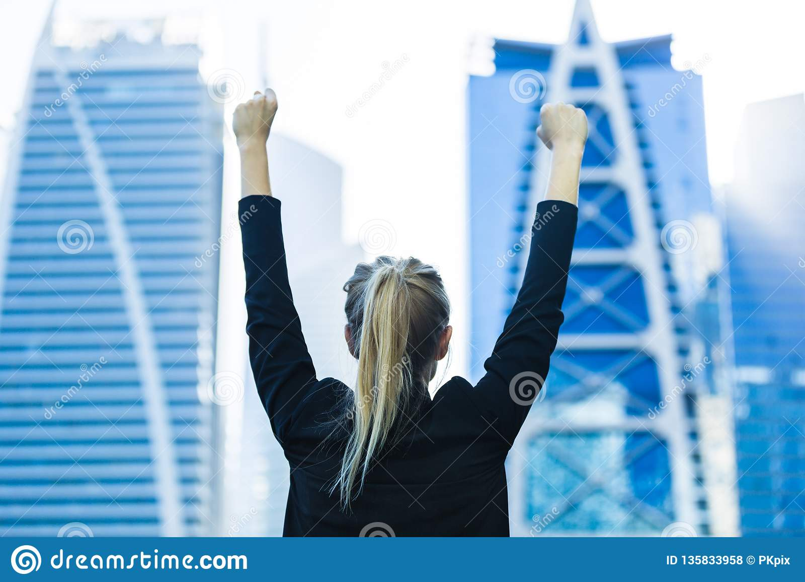 企业成功-庆祝俯视市中心高层的女实业家