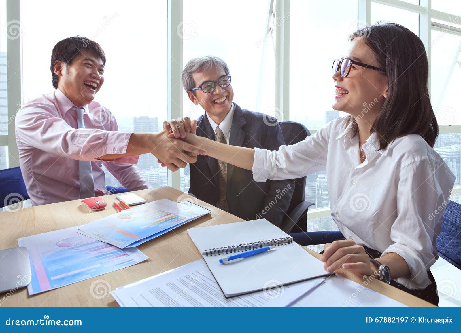 企业握手的队工作在办公室有happ的会议室