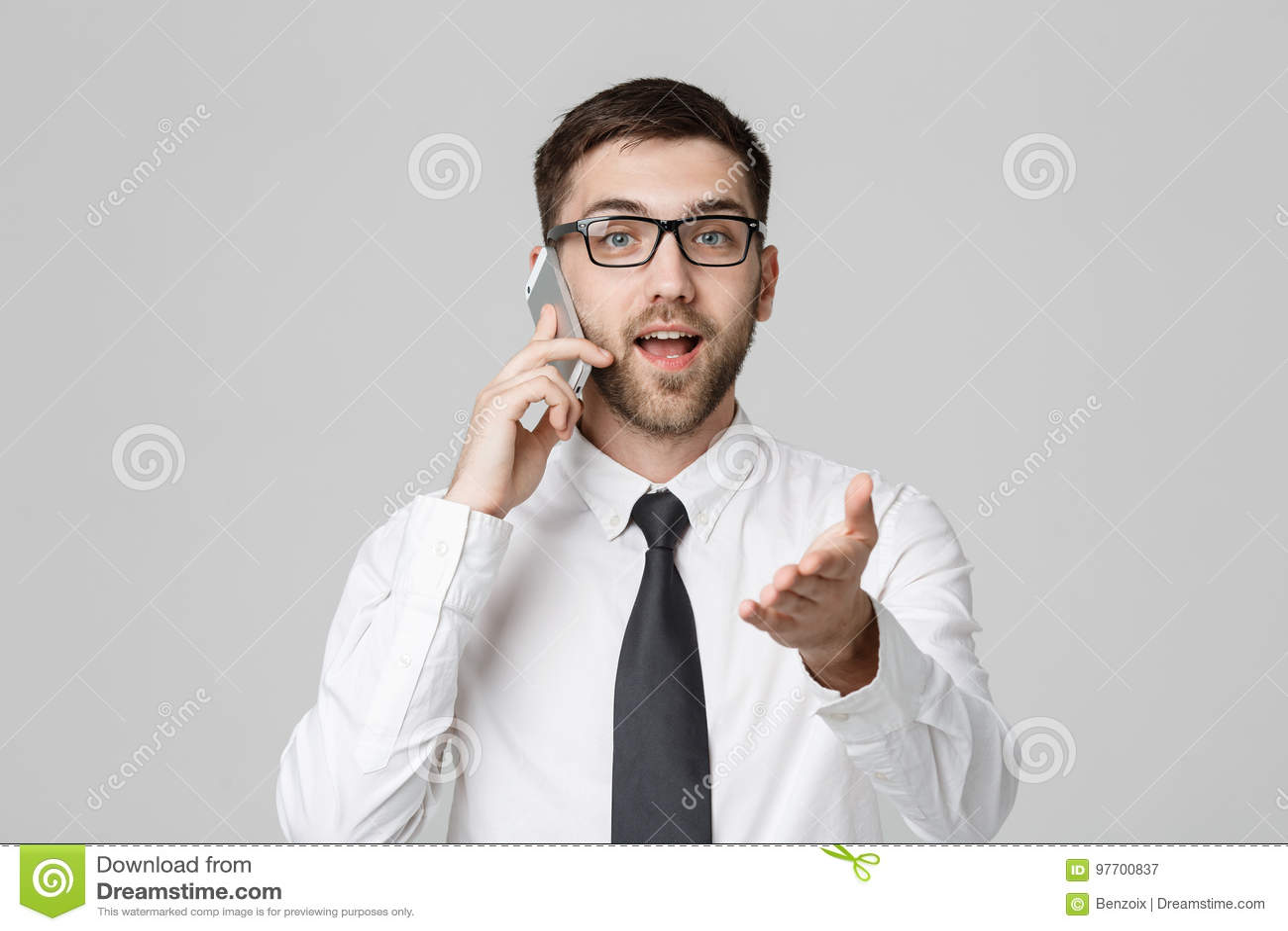 企业概念-衣服的画象年轻英俊的恼怒的商人谈话在看照相机的电话 奶油被装载的饼干