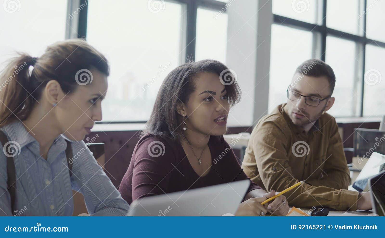 企业队会议在现代办公室 创造性的年轻混合的族种人谈论新的想法与经理