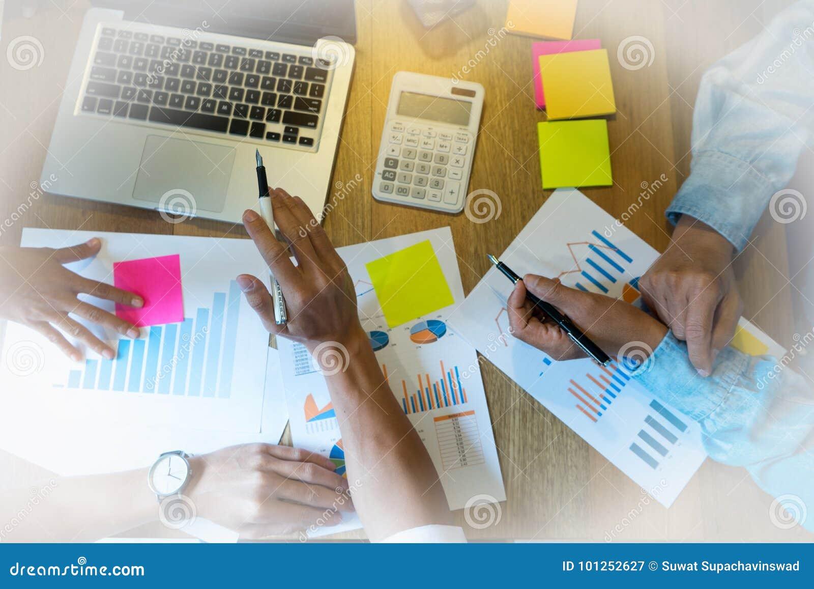 企业队男人和妇女与在木桌上的膝上型计算机一起使用