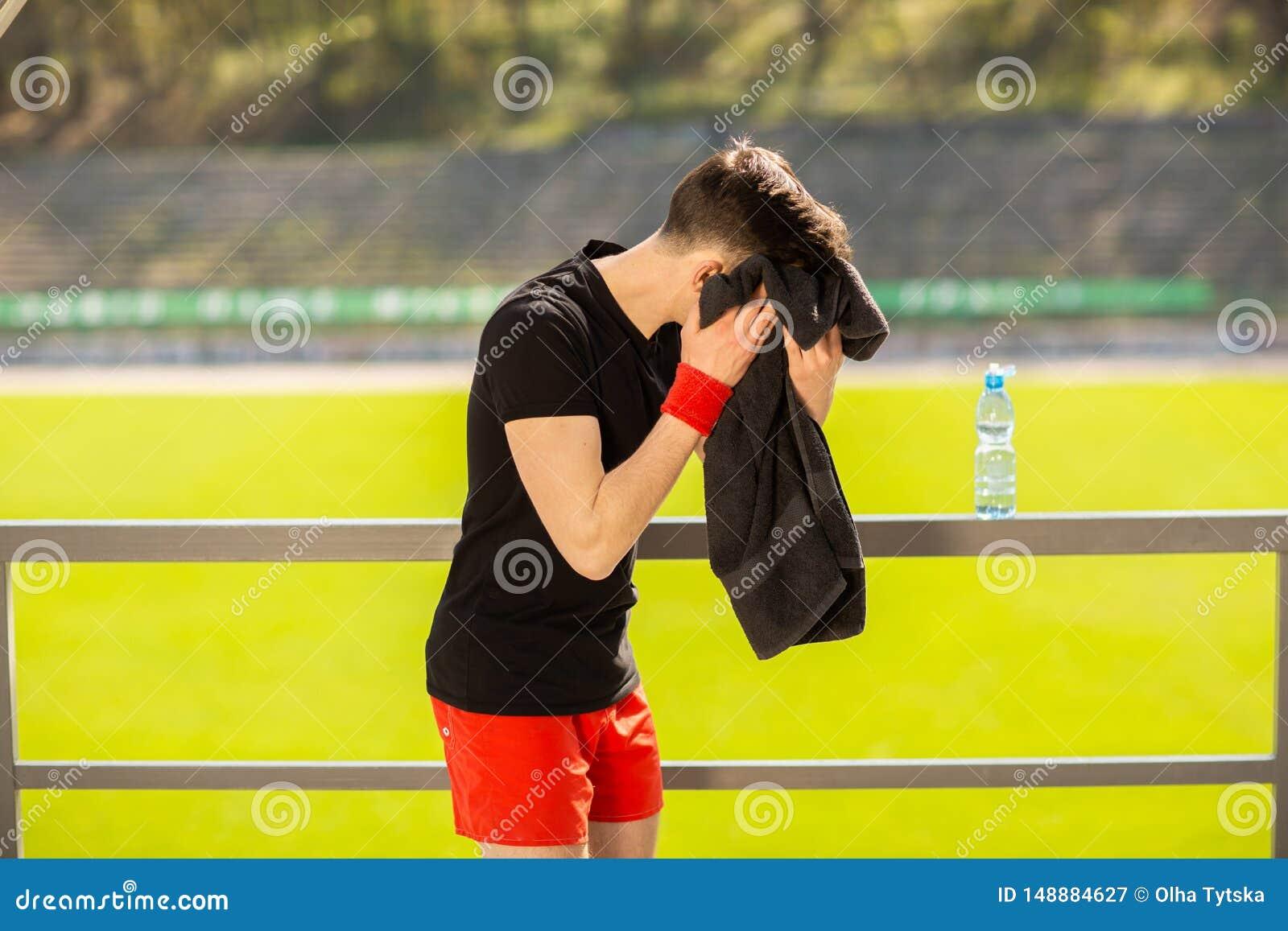 休息和抹他的汗水的年轻运动的人与毛巾在锻炼体育锻炼以后户外