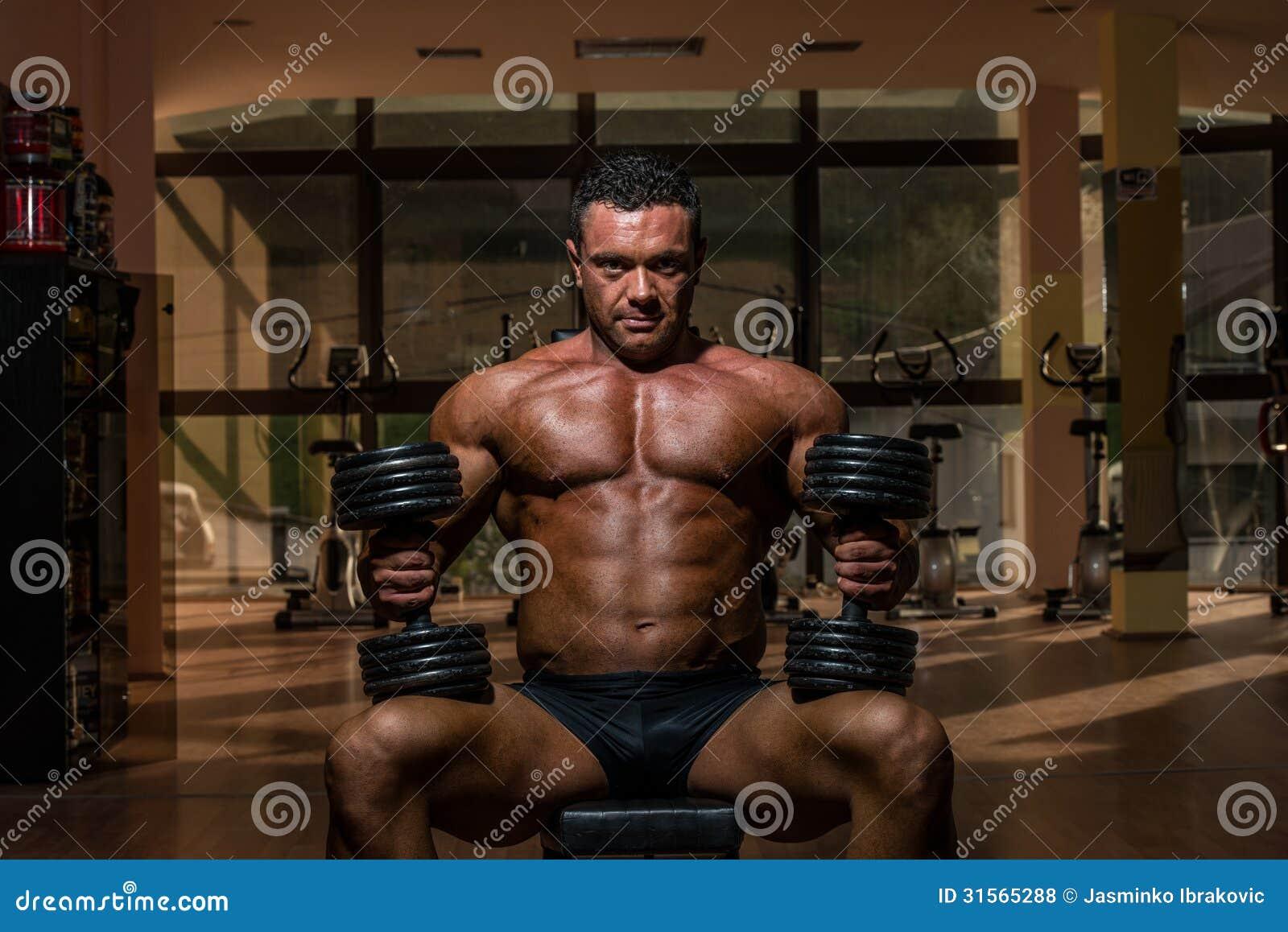休息在做的男性爱好健美者重量级的锻炼以后
