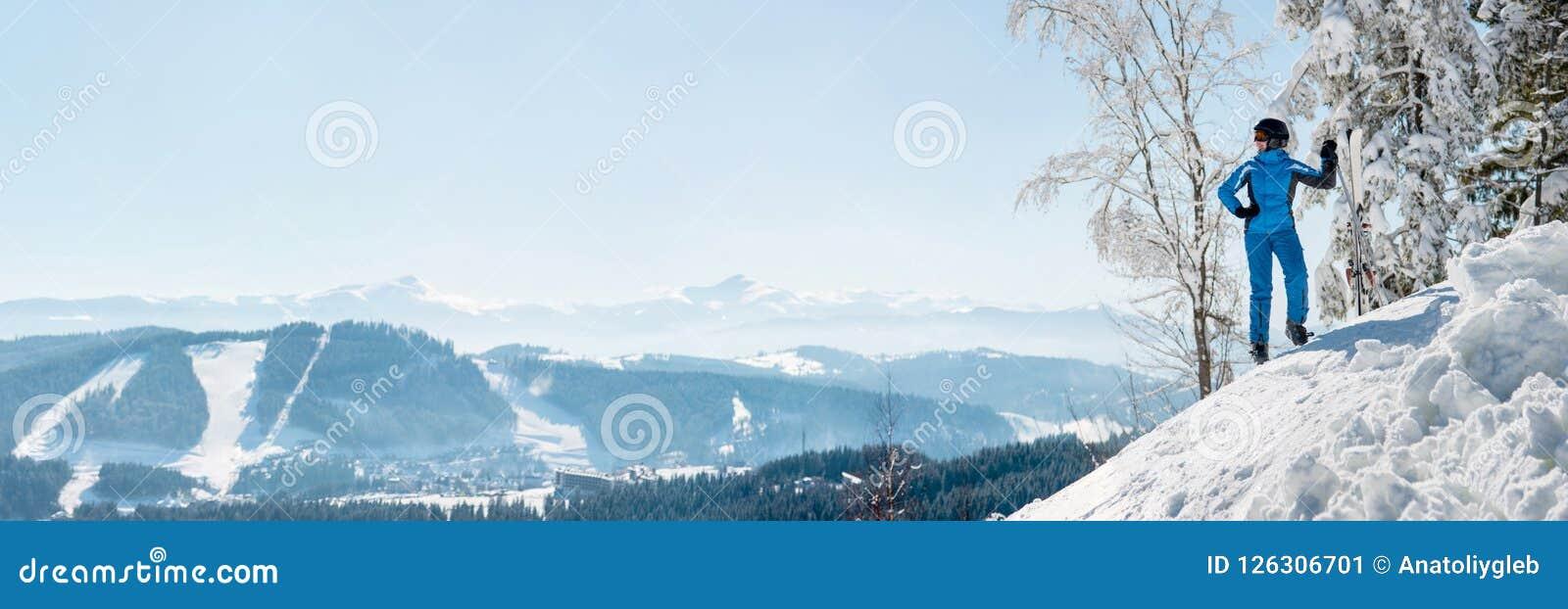 休息在山顶部的一个女性滑雪者的全景射击观察自然在滑雪胜地