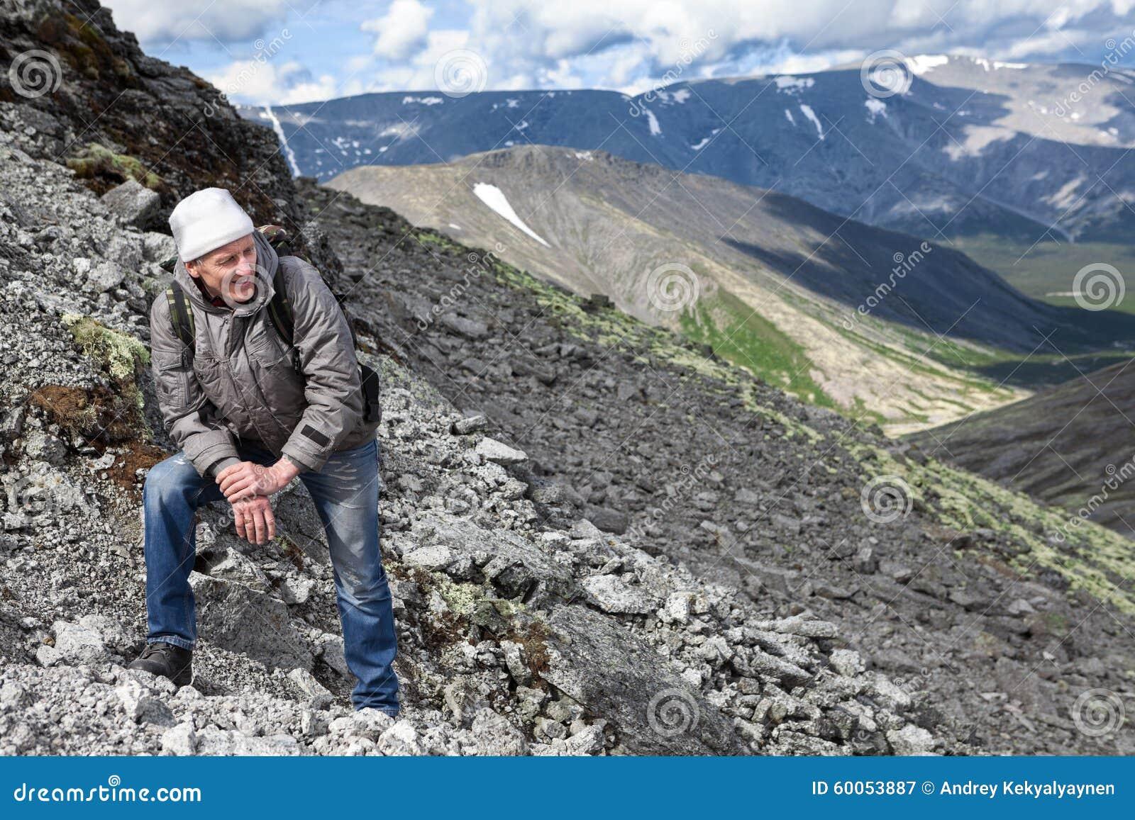 休息在重上升的旅游远足者在山的陡坡期间