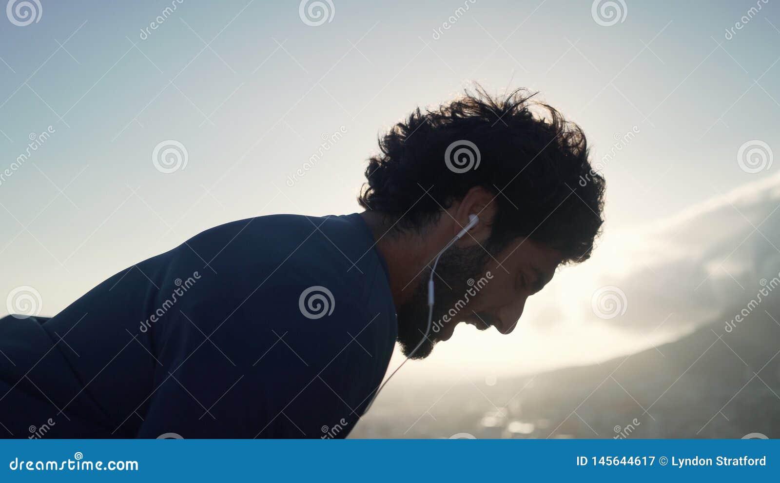 休息在锻炼以后的一个微笑的男性赛跑者在户外