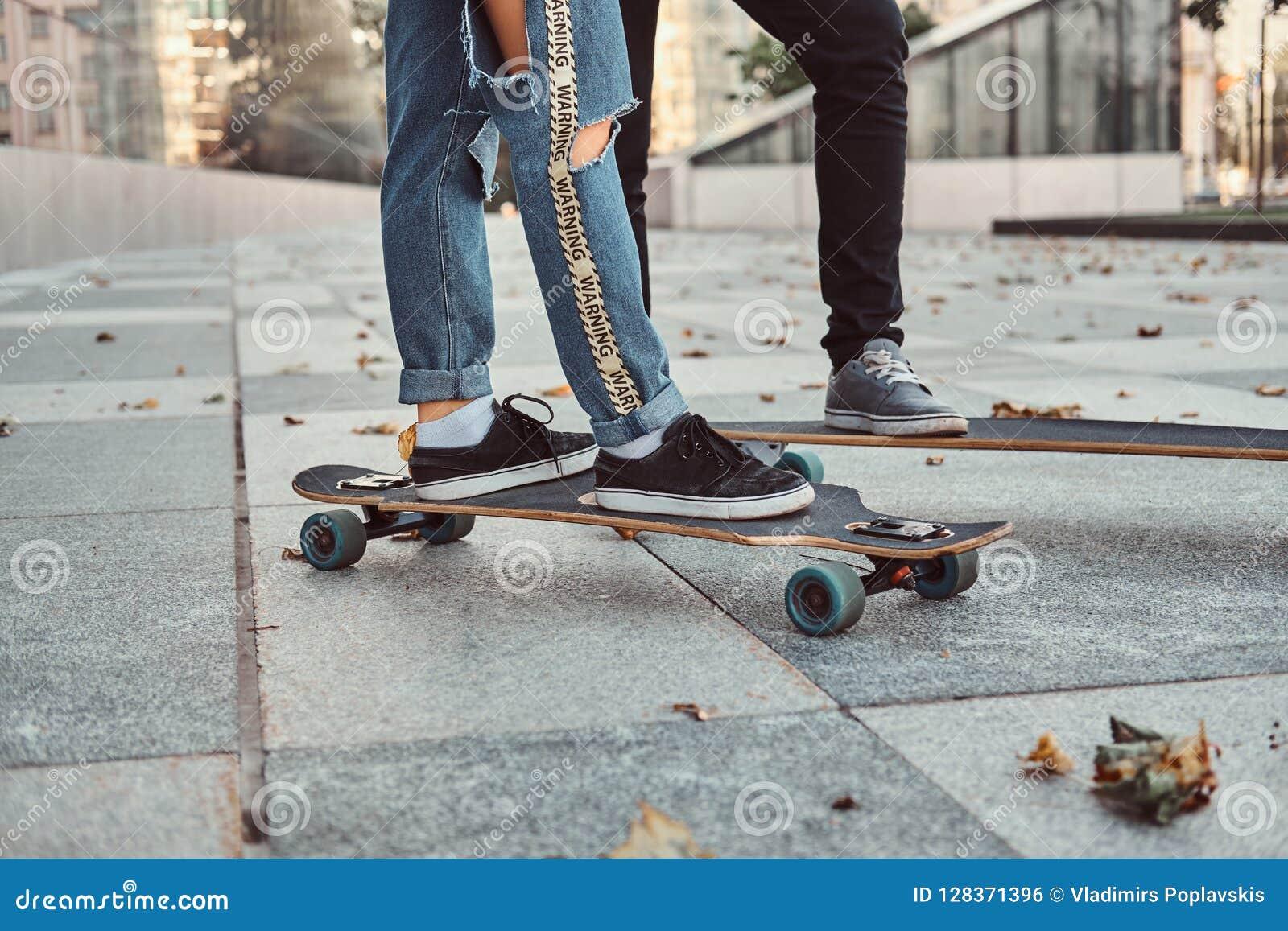 休闲和体育概念-一时髦穿戴的青少年的加上的特写镜头照片在街道上的滑板