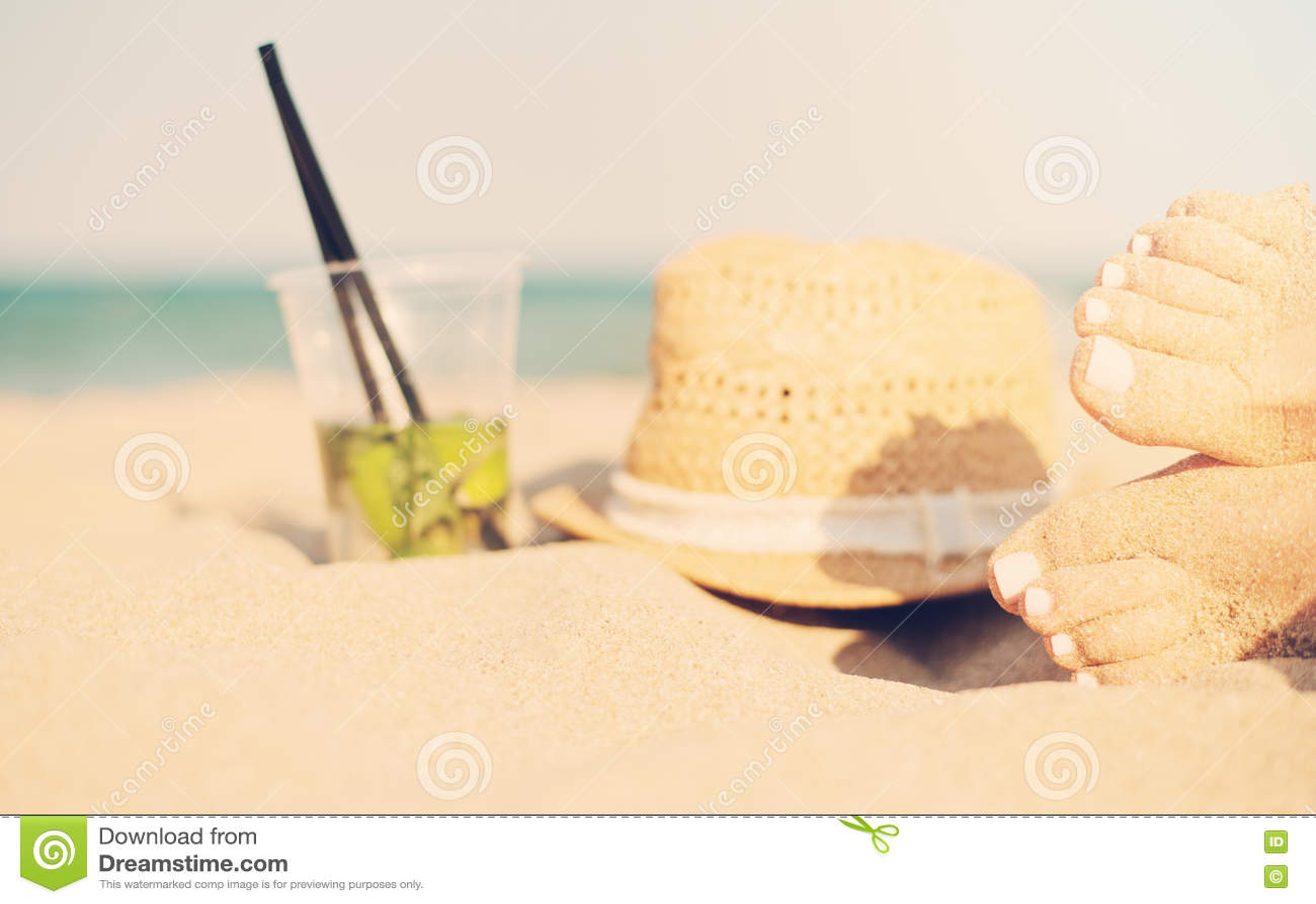 休闲在夏天-美好性感的妇女脚、女性腿在沙滩与帽子和mojito鸡尾酒 在的Mojito鸡尾酒