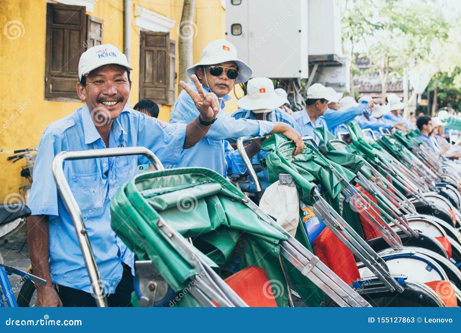 会安市,越南- 2019年6月:越南人力车微笑并且显示胜利标志用他的手