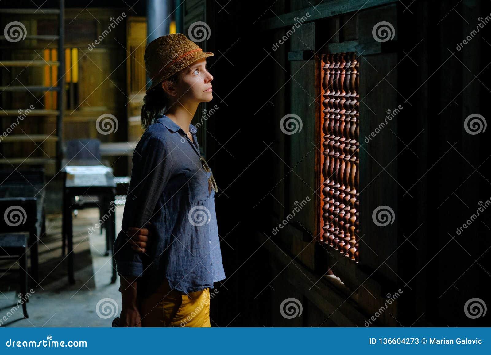 会安市/越南,11/11/2017:在一个传统房子Tan Ky的黑暗的木内部的女性旅游身分在会安市,