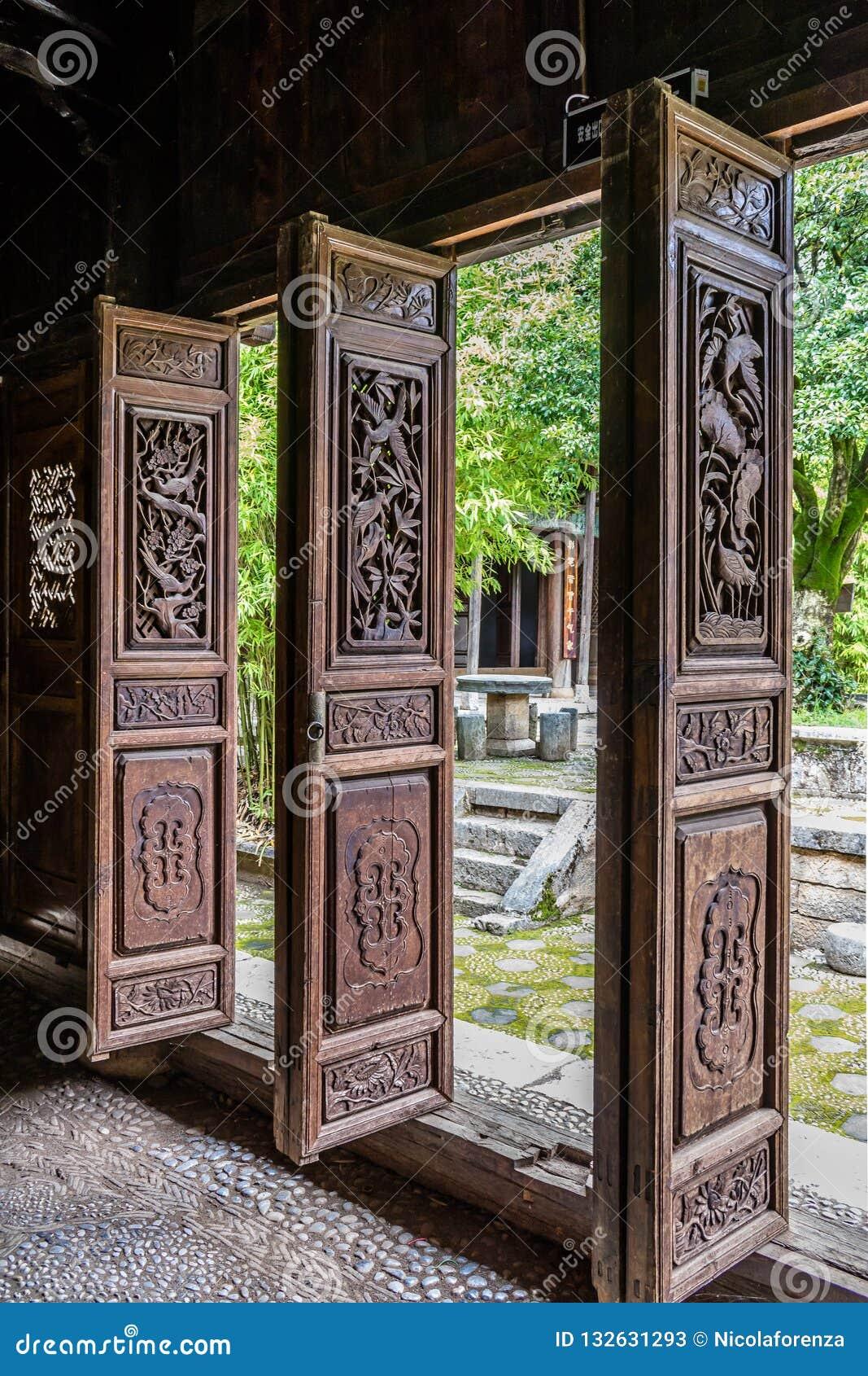 传统中国木被雕刻的门在庭院打开了