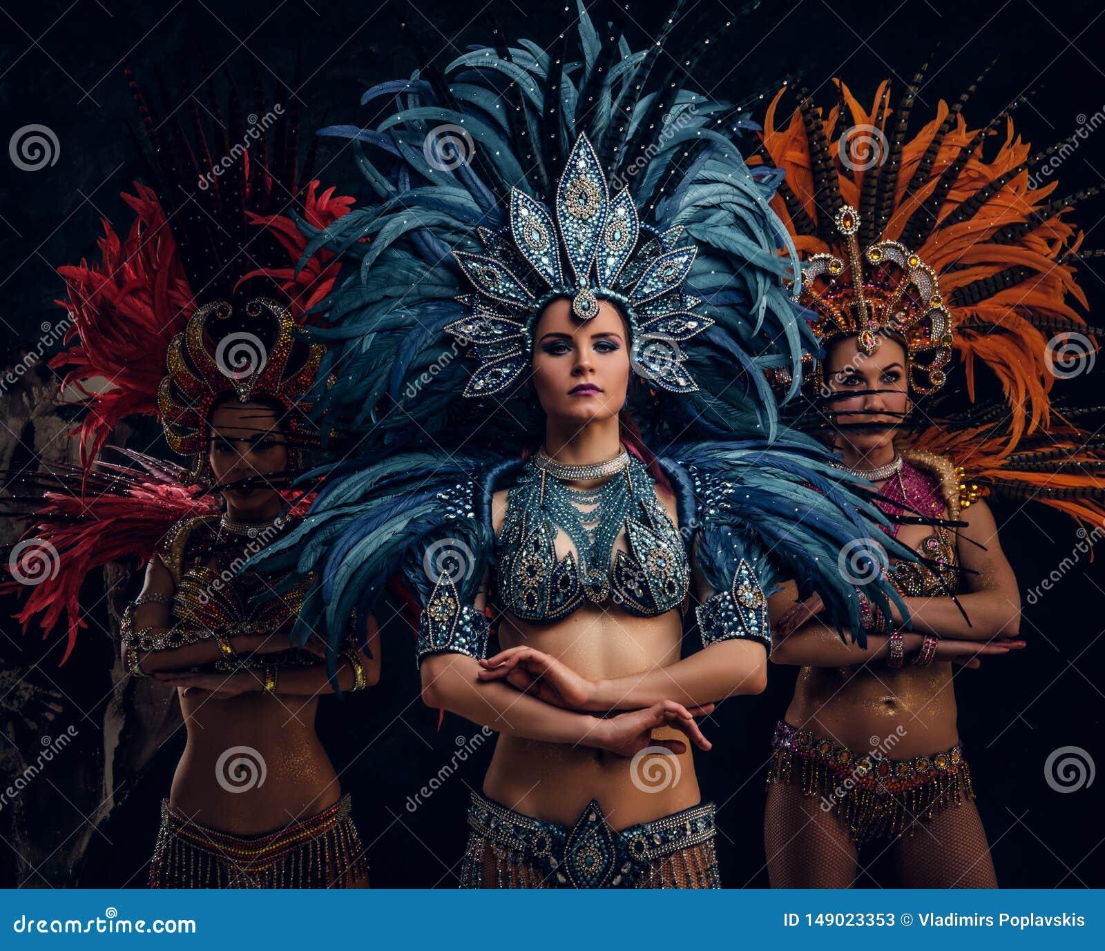 传统brasilian carnaval服装的三美女为摄影师摆在演播室
