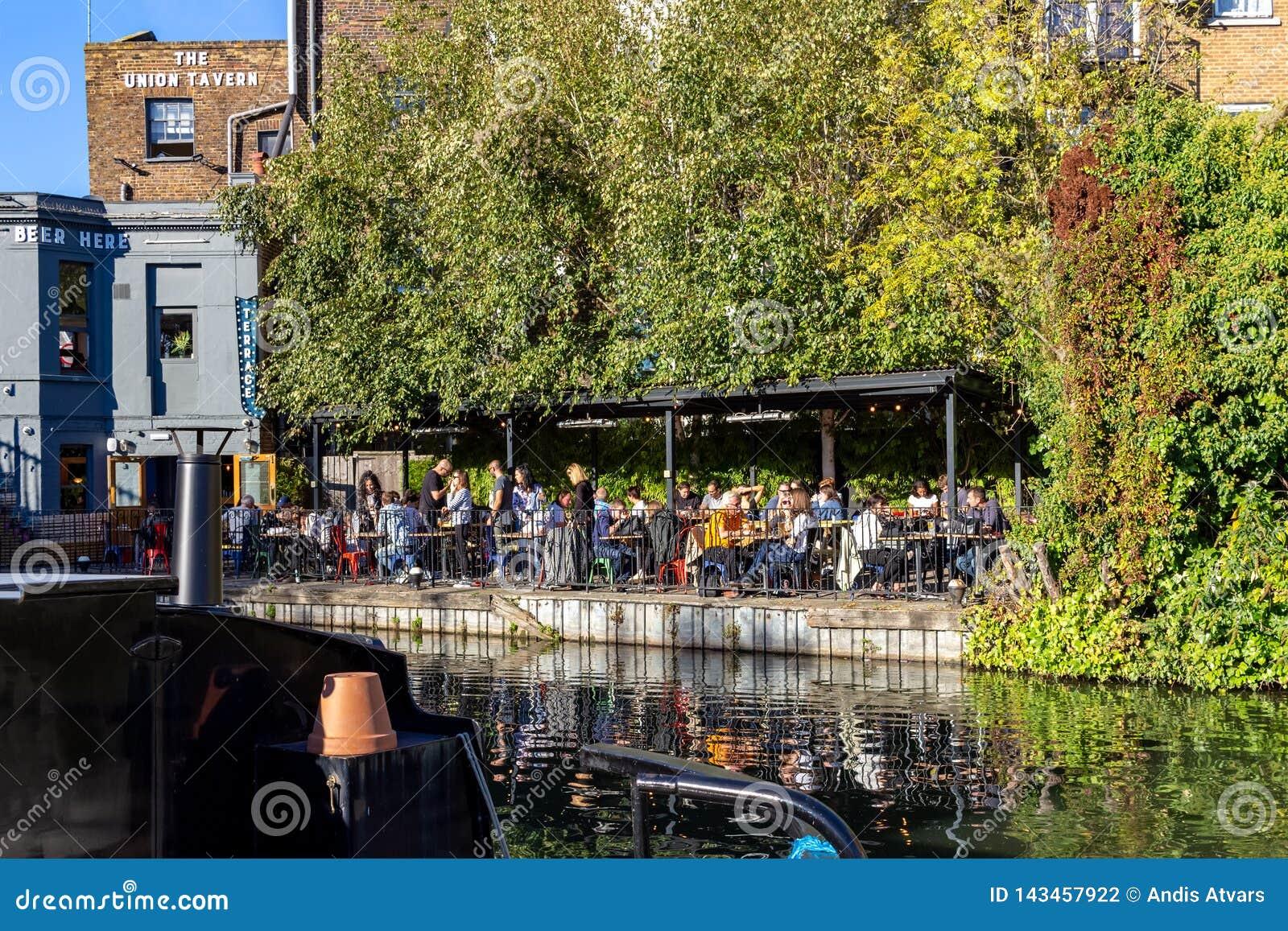 伦敦,英国–2018年10月21日:人们吃午餐在运河银行的一个小酒馆在董事的运河在帕丁顿旁边在小