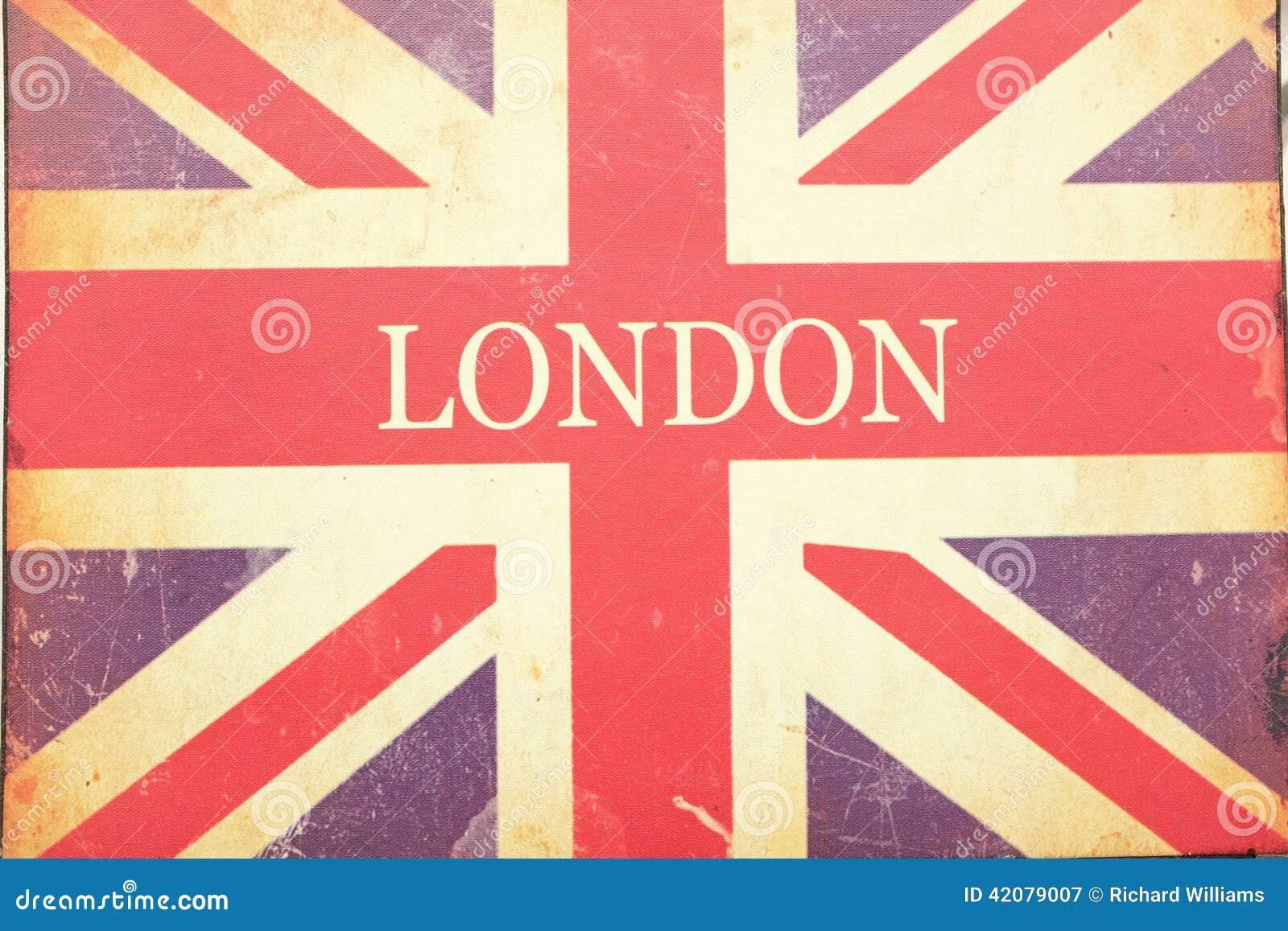 伦敦和英国国旗在老被编织的织品签字以污点和抓痕.图片