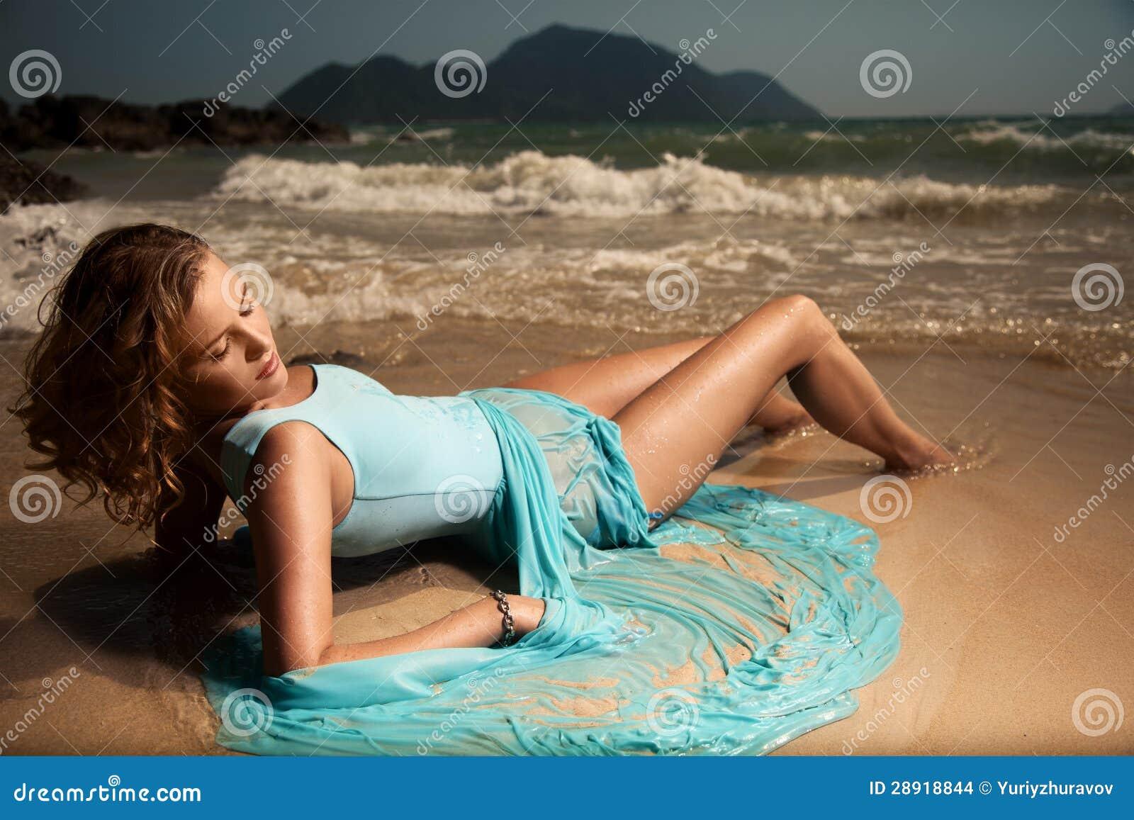 位于在沙子热带B的蓝色礼服的方式妇女