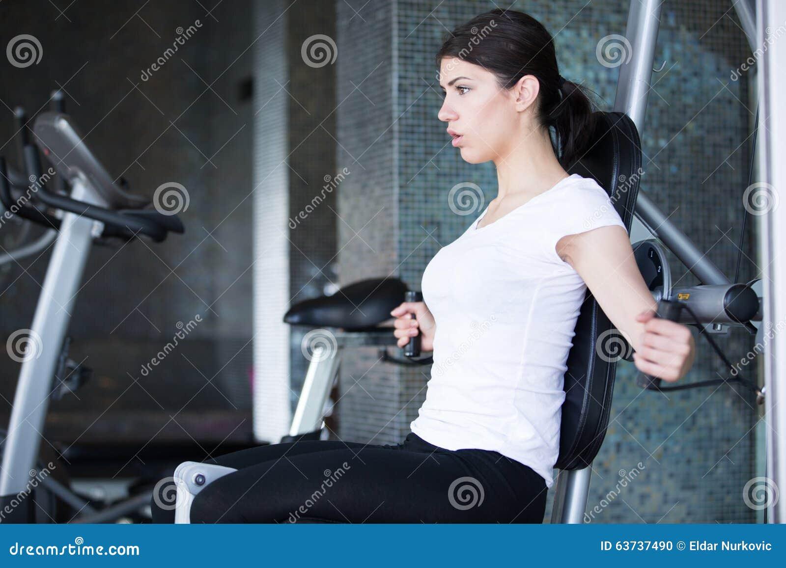 体操培训重量妇女 行使拉下重量机器 做引体向上的妇女行使举的哑铃
