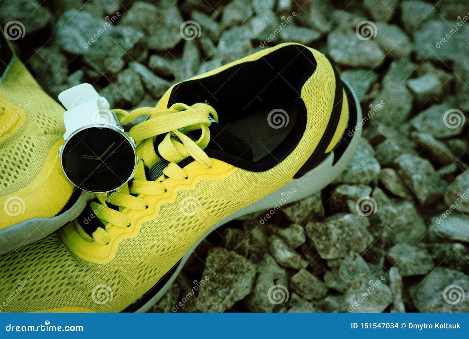 体育在黄色跑鞋的注意crossfit和三项全能 巧妙的注意跟踪的每日活动和力量训练
