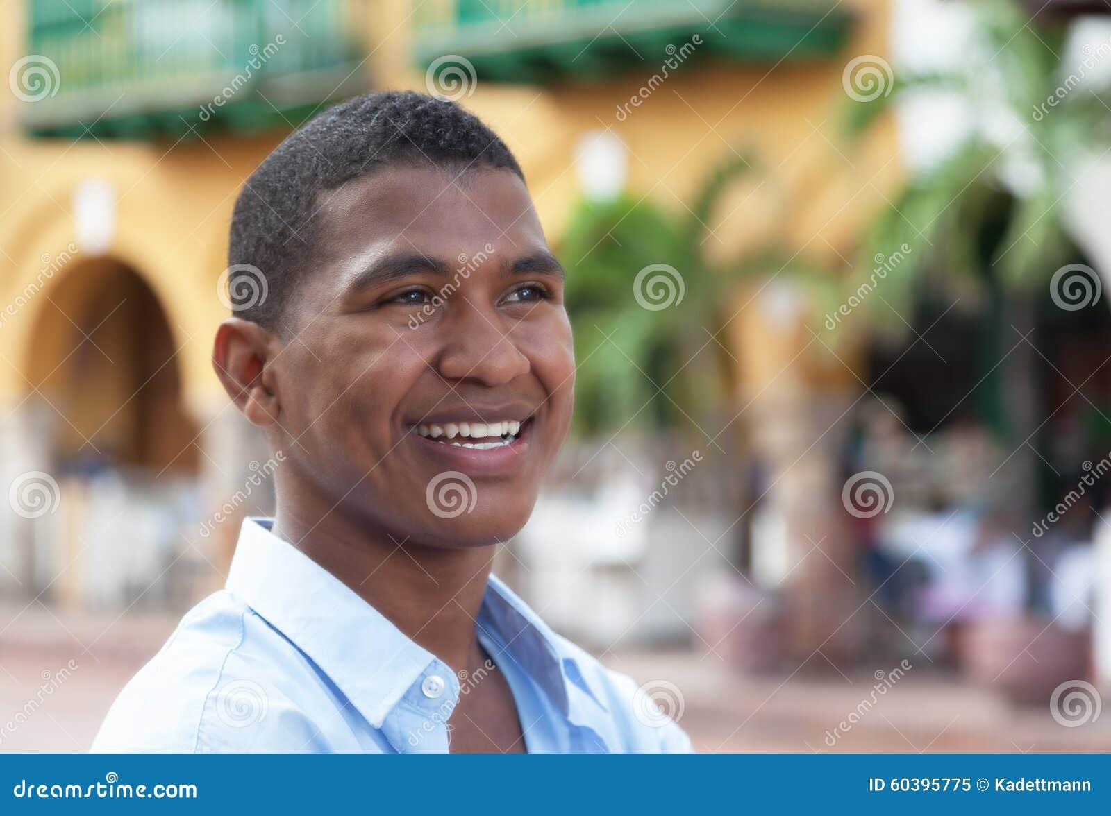 作一件蓝色衬衣的人在一个五颜六色的殖民地镇