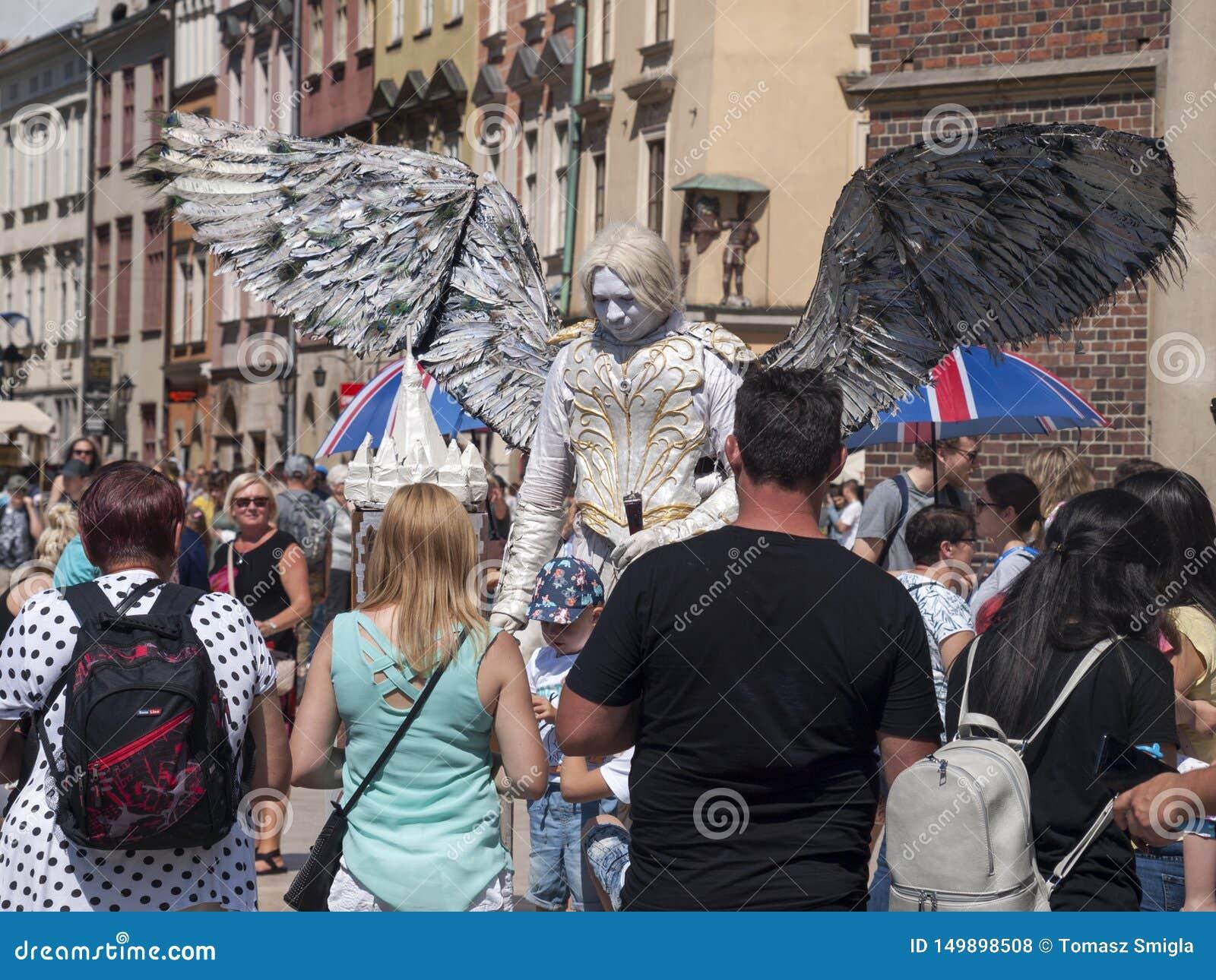 作为与的一个天使打扮的卖艺人/街道执行者巨大的翼,围拢他的人群等待拍照片