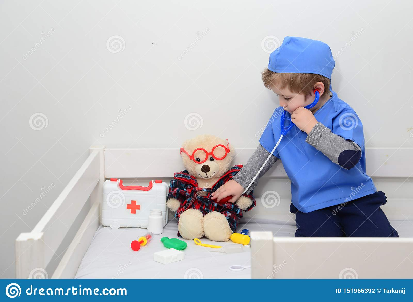 ?? 作为医生打扮的可爱的孩子使用与玩具 由年轻医护人员的健康检查 教育和