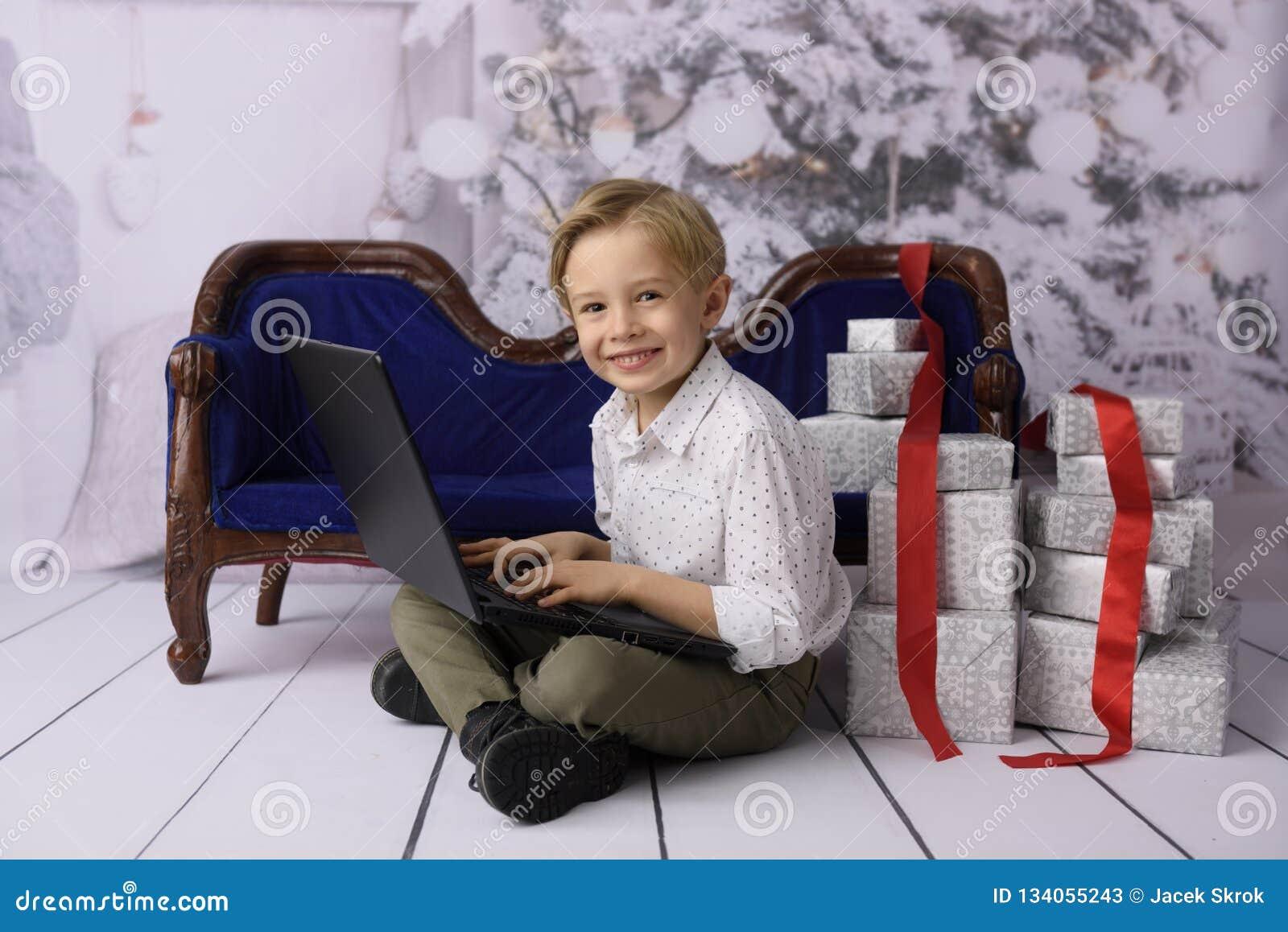 作为圣诞老人项目的一个微笑的男孩与一棵圣诞树在背景中