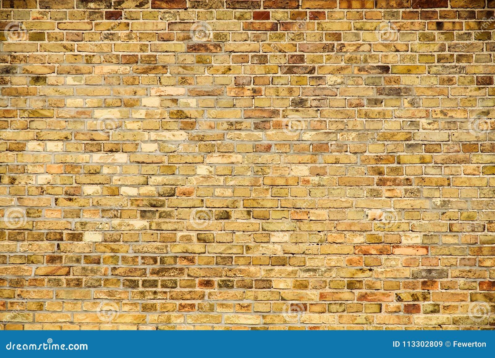 作为无缝的样式纹理背景的老和被风化的脏的黄色和红砖墙壁