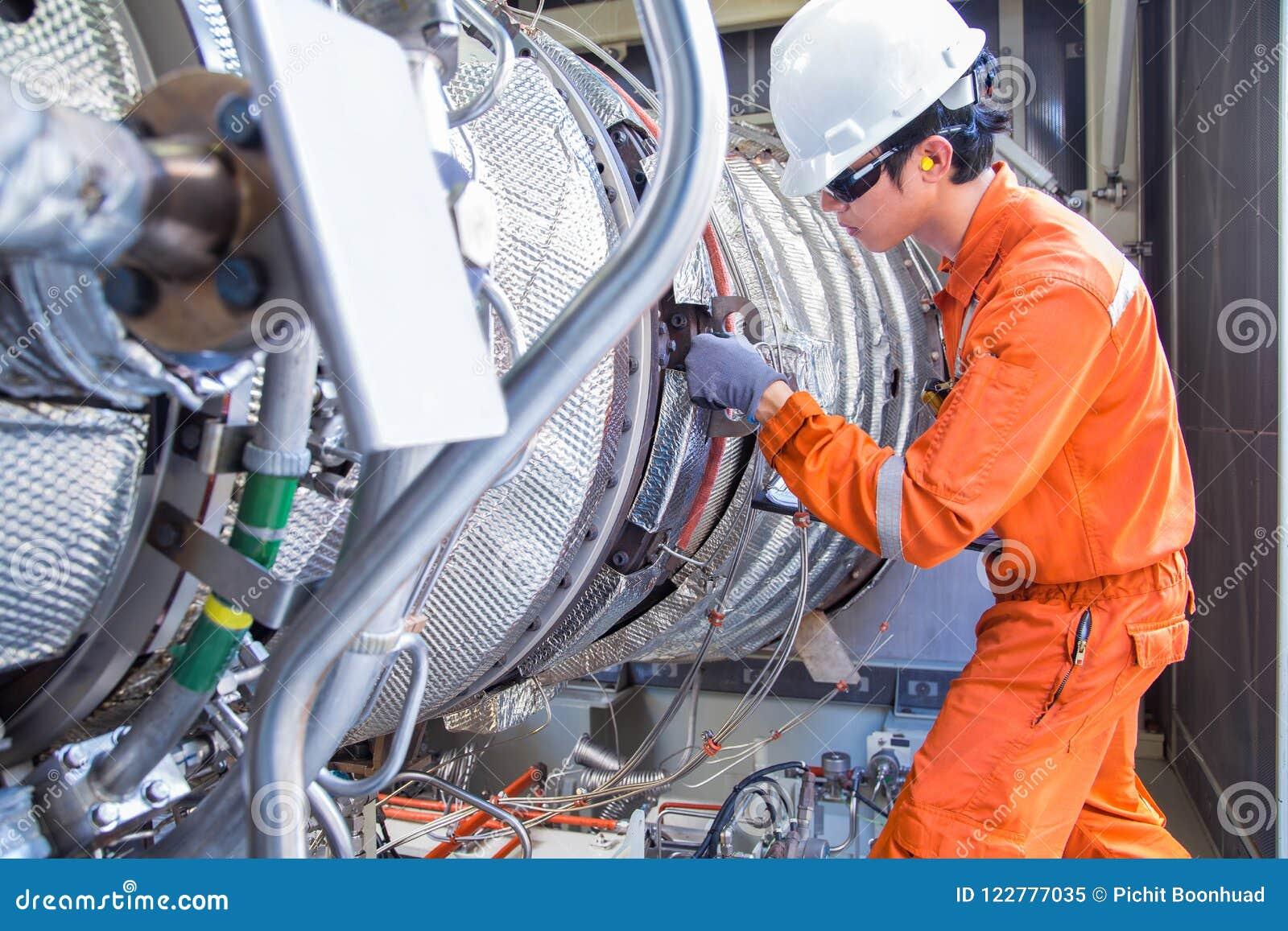 佩带个体防护用品的涡轮工程师检查汽轮机引擎在近海油和煤气中央平台